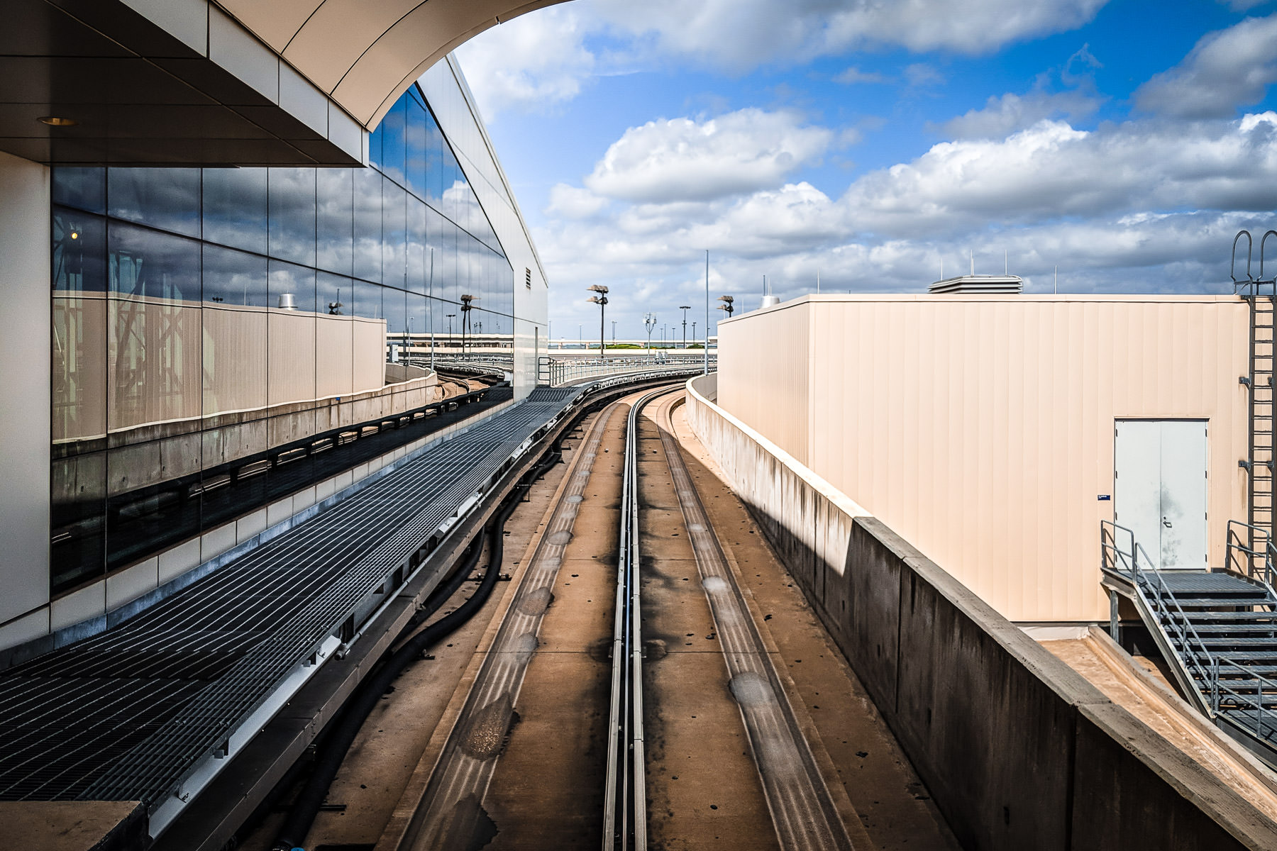 Tracks for the Skylink train lead away from a terminal at DFW International Airport, Texas.