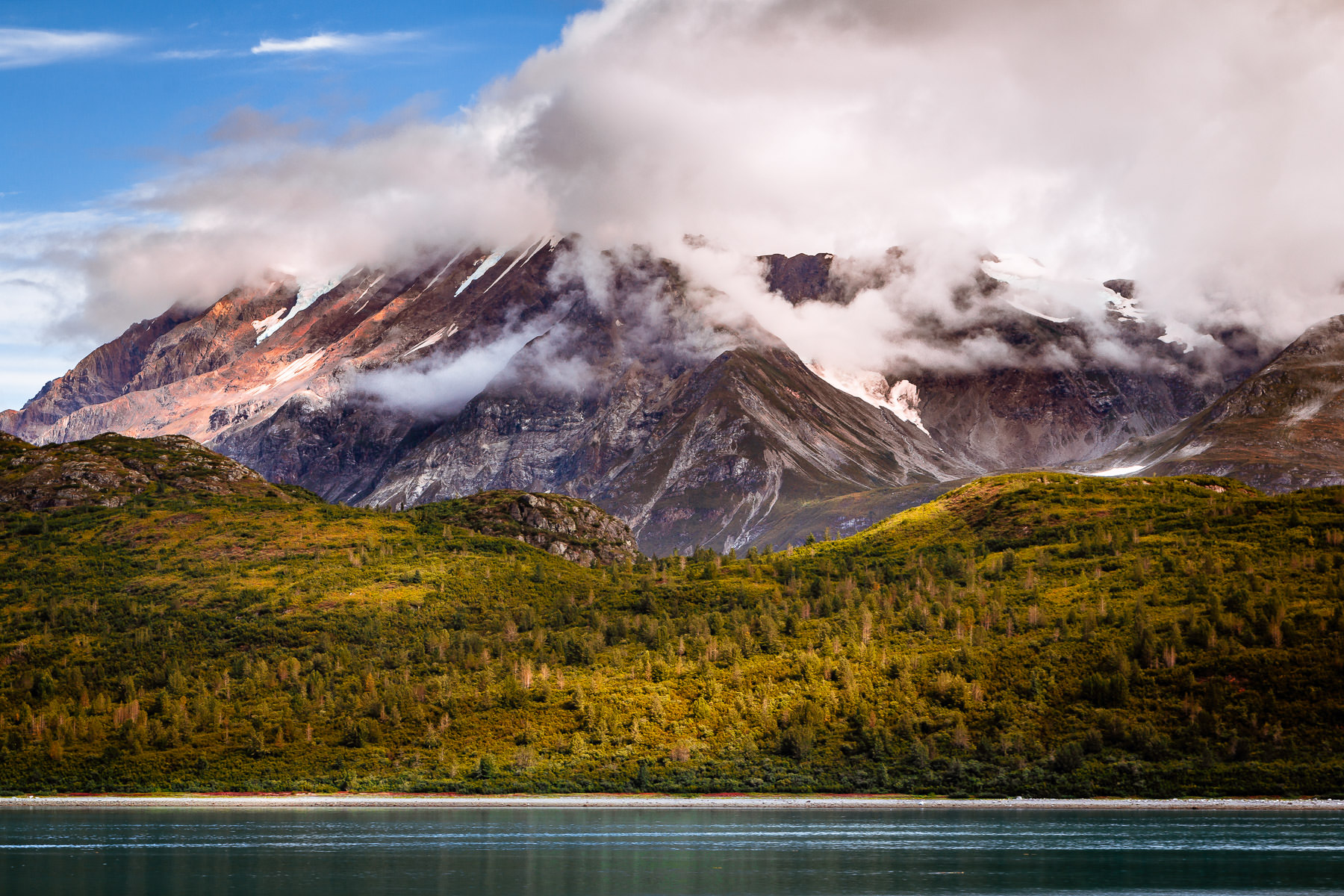 A mountain rises into the clouds at Glacier Bay National Park, Alaska.