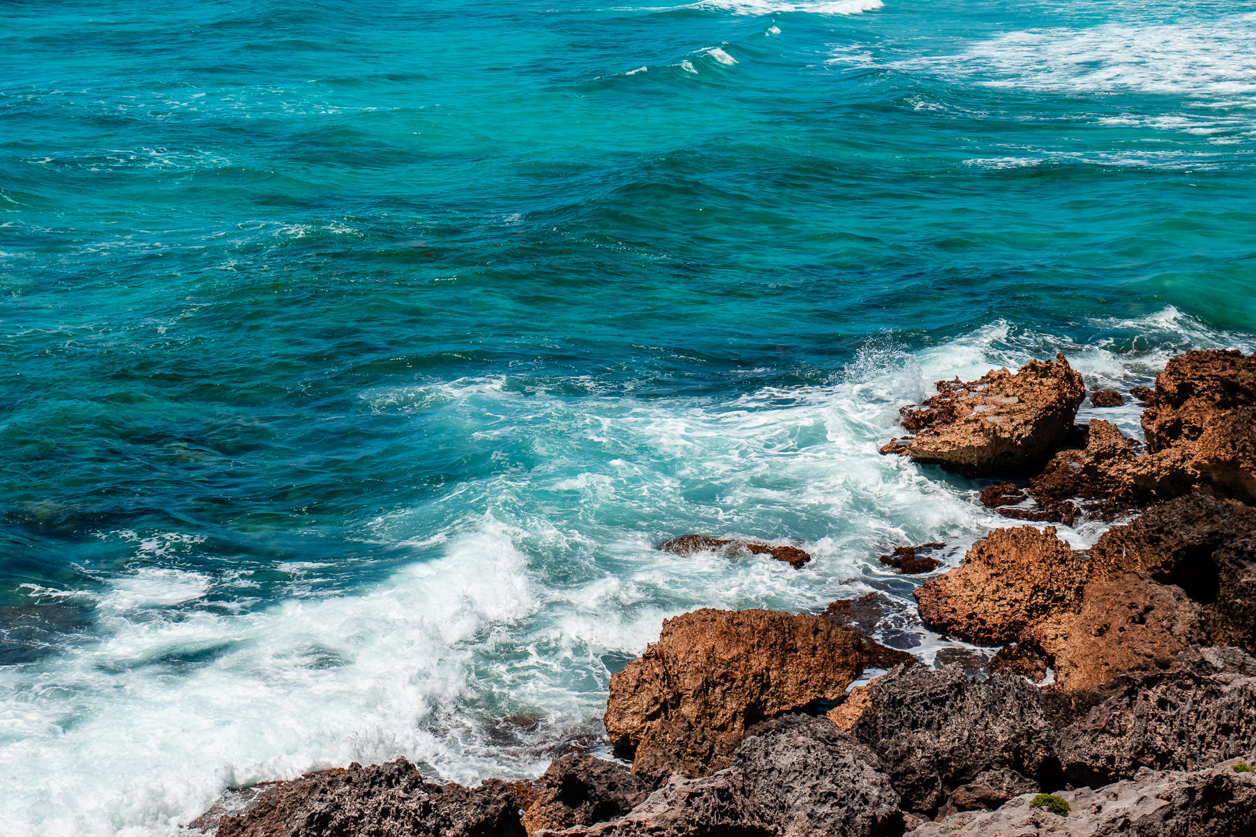 Waves froth against rough rocks on the eastern shore of Cozumel, Mexico.