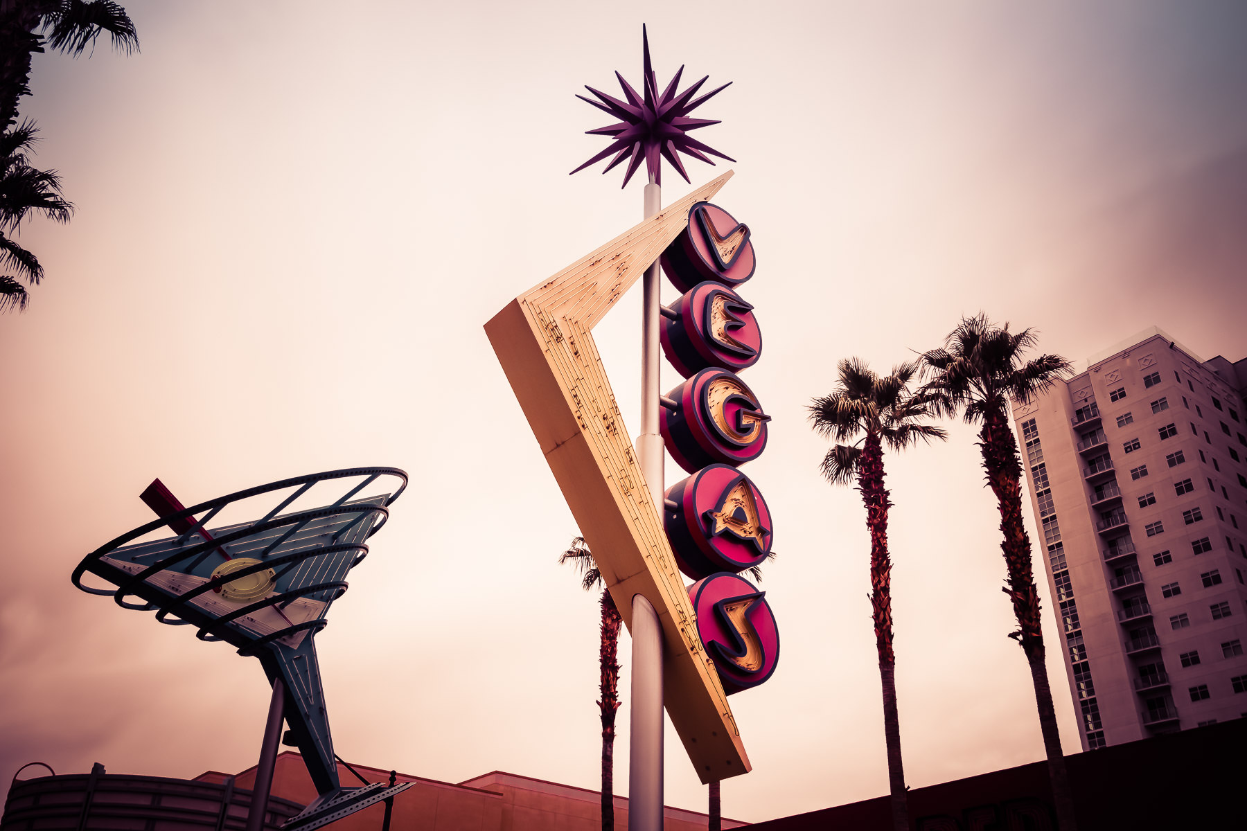 A Googie-styled sign rises into the Downtown Las Vegas sky.