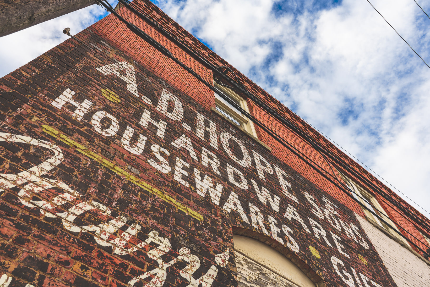An old faded sign painted on the side of a building in Downtown McKinney, Texas.