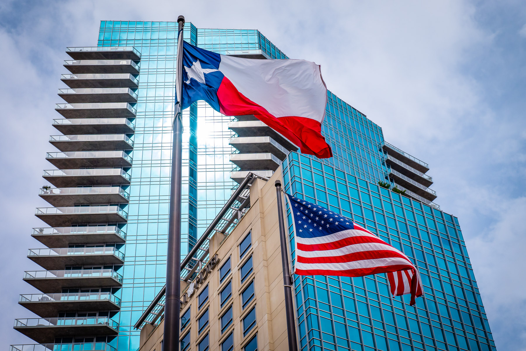 The Omni Fort Worth Hotel rises above the Texas Flag and the United States Flag.