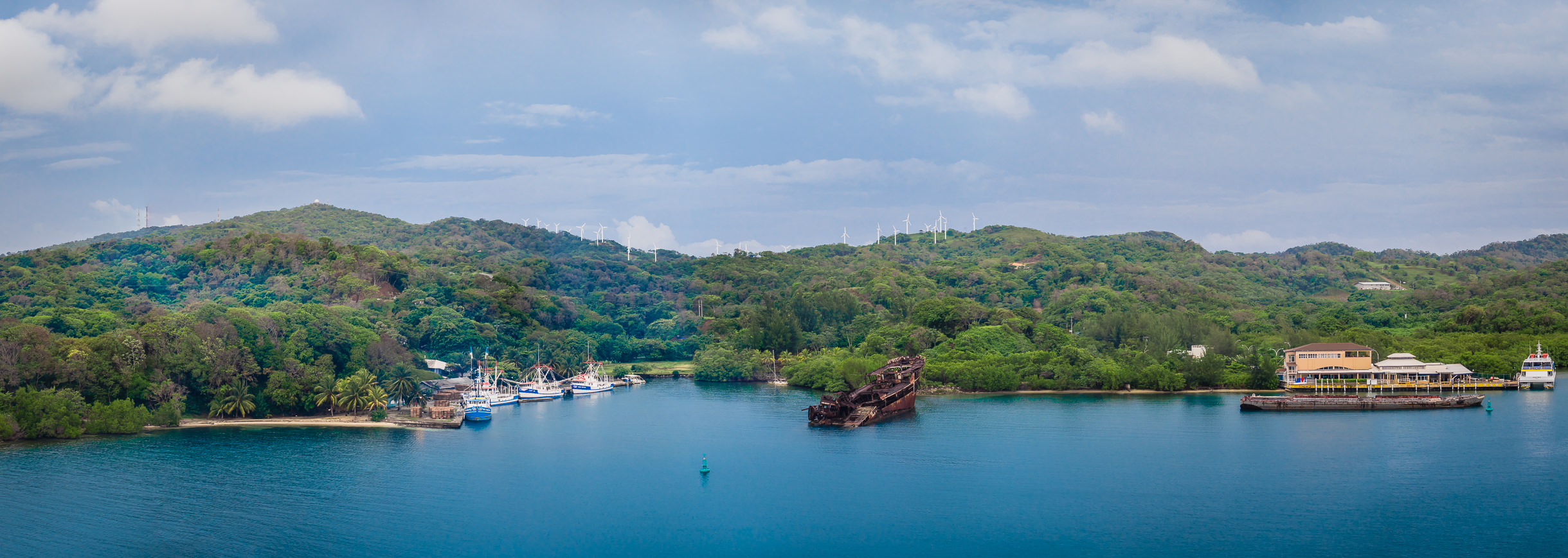 A partially-sunken ship rises from the waters of Roatan, Honduras' harbor.
