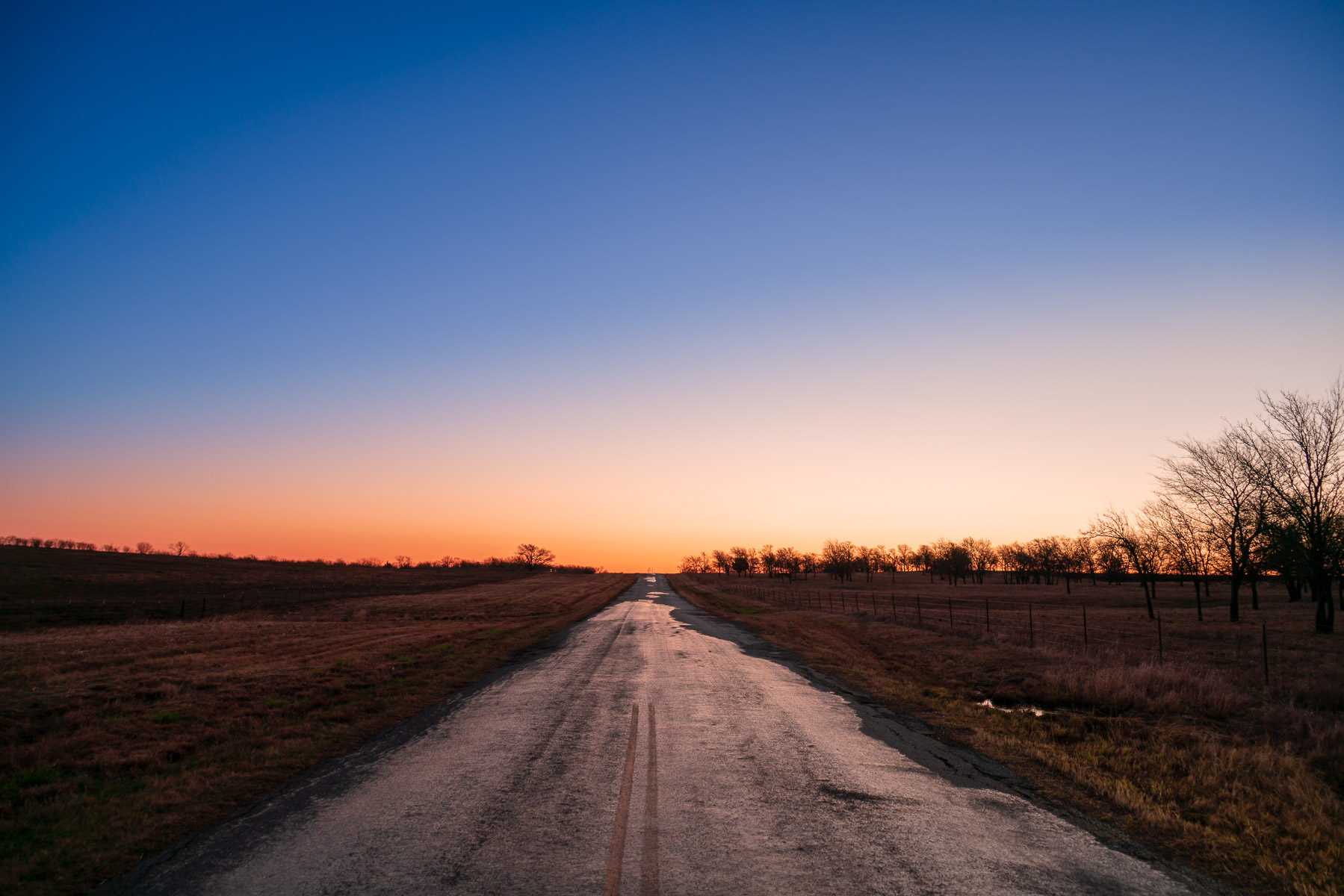 The first light of the day begins to illuminate a country road in North Texas.