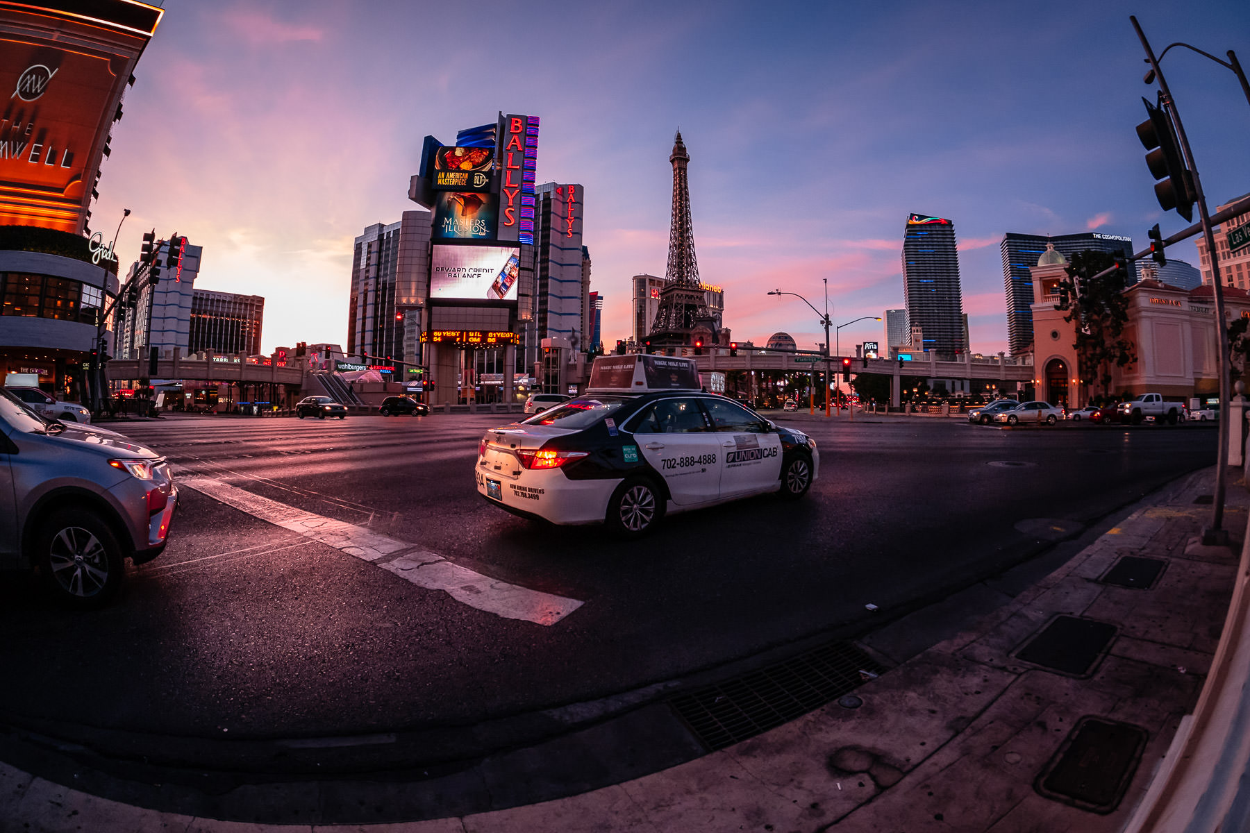 A taxi waits at a traffic light as the sun begins to rise on the Las Vegas Strip.