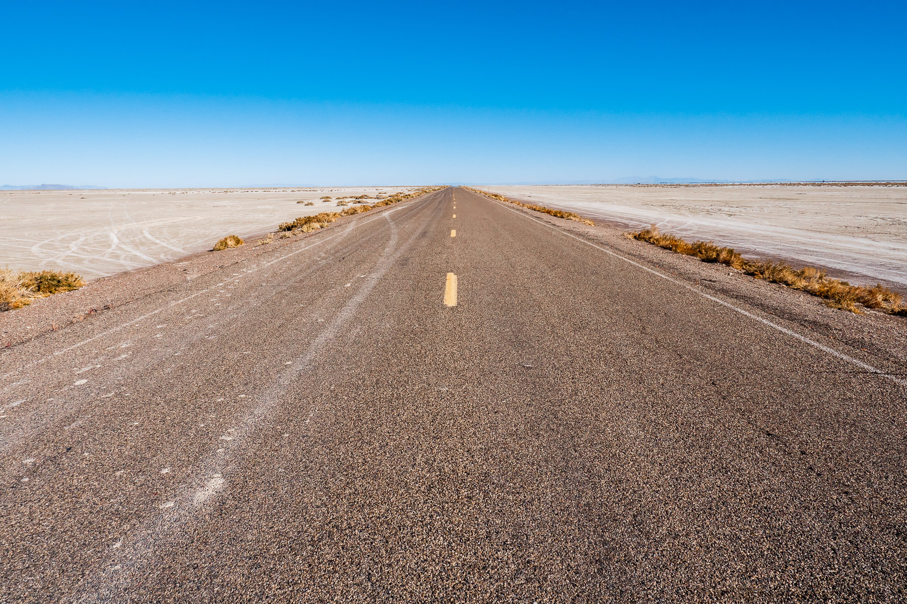 A road stretches across the arid expanse of Utah's Bonneville Salt Flats.