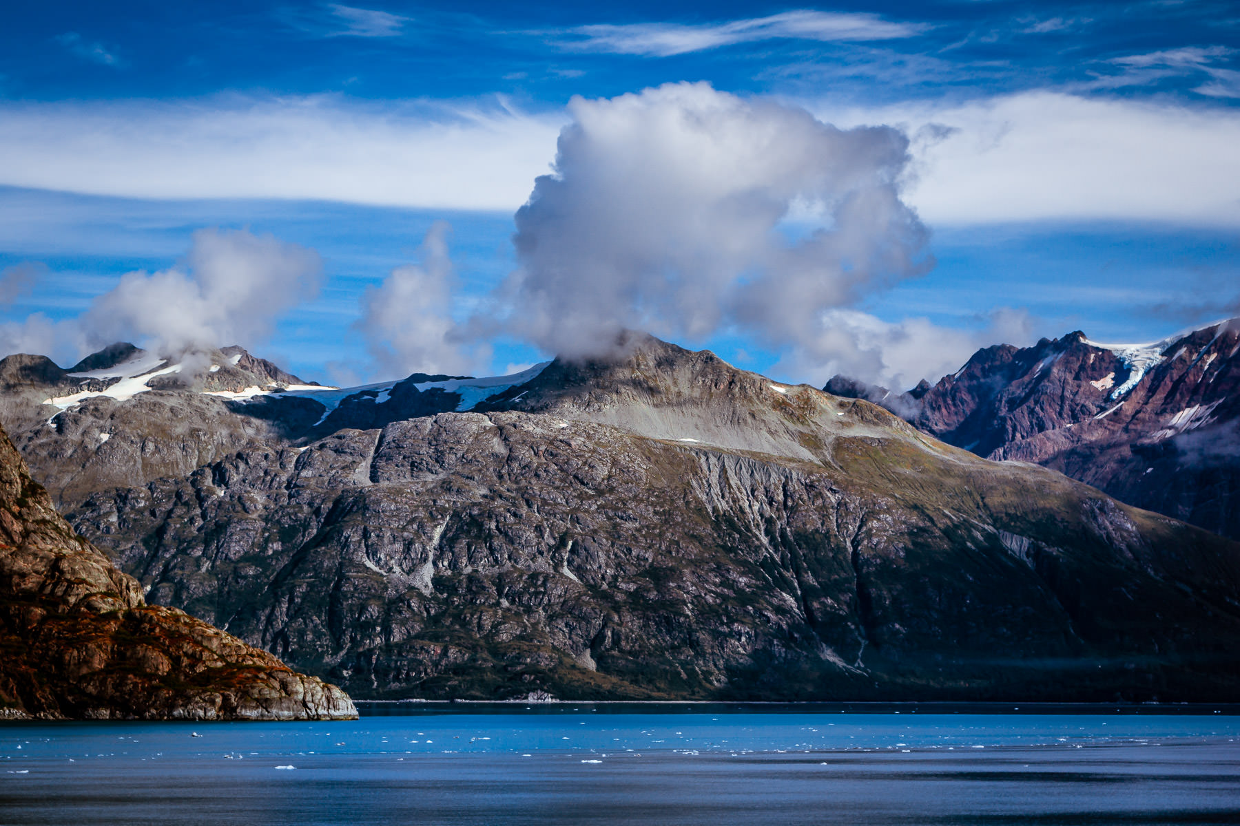 Mountains rise from the shore of Alaska's Glacier Bay to reach to the clouds above.