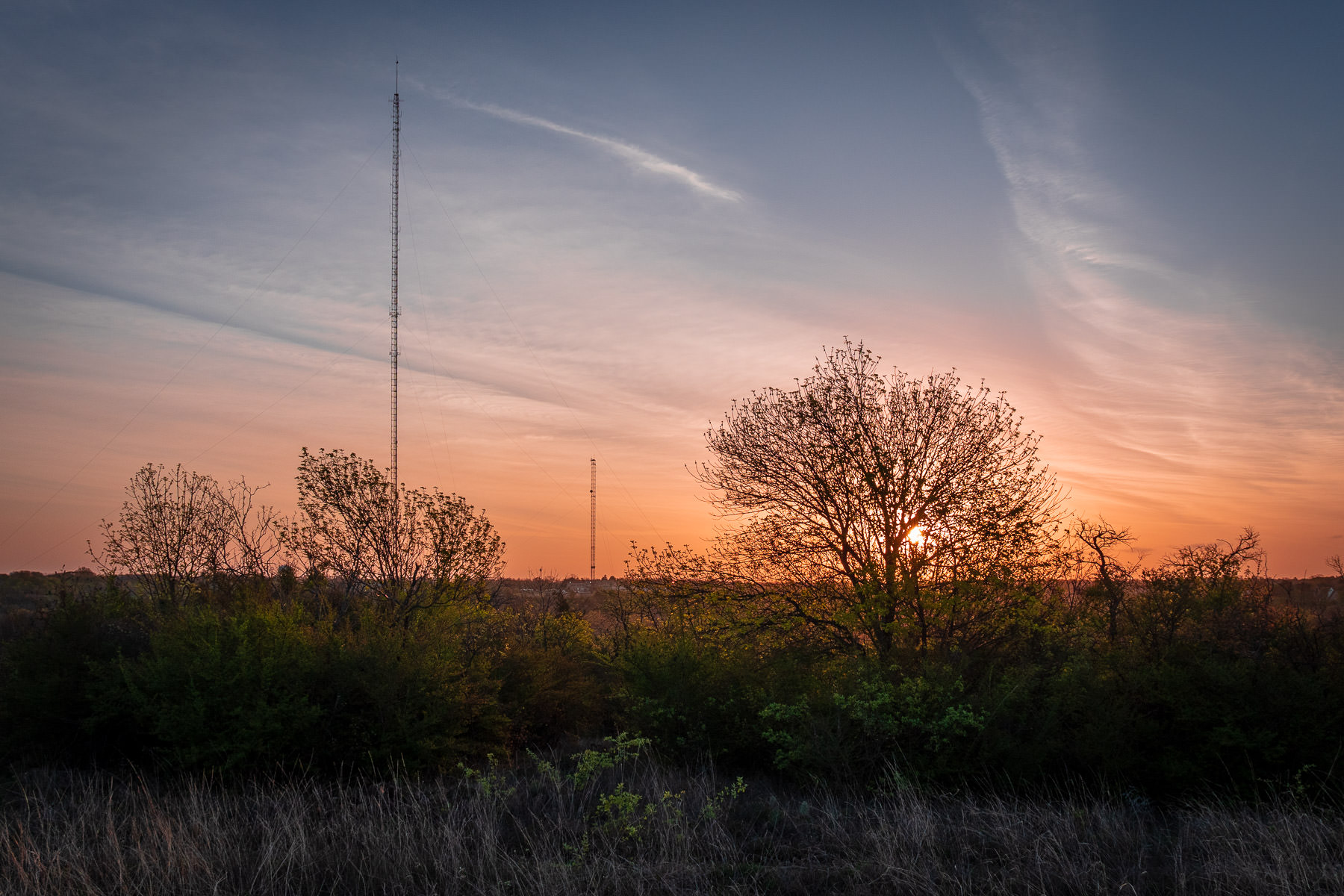 Broadcast towers rise into the sky as the sun rises over Fort Worth, Texas' Tandy Hills Natural Area.
