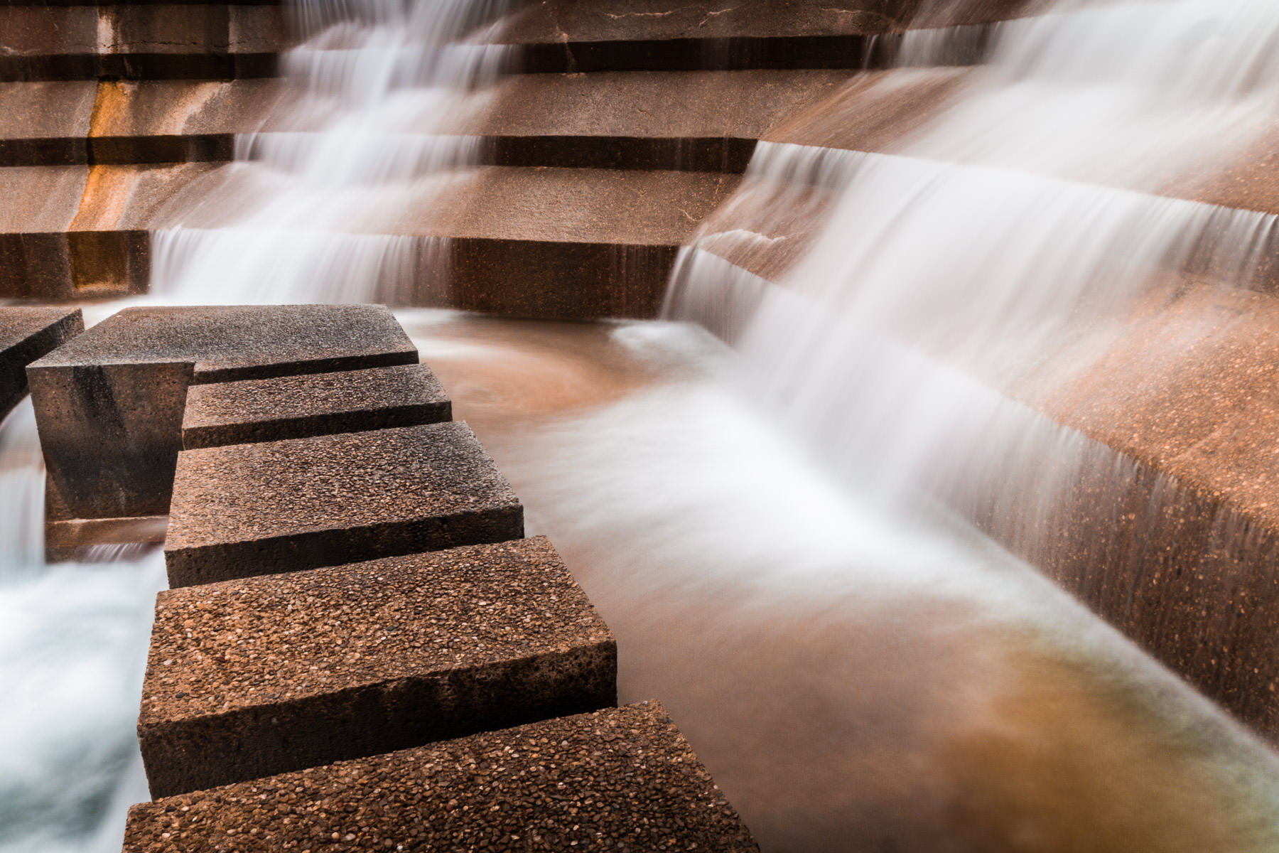 Water spills down the concrete facets of the Fort Worth Water Gardens.