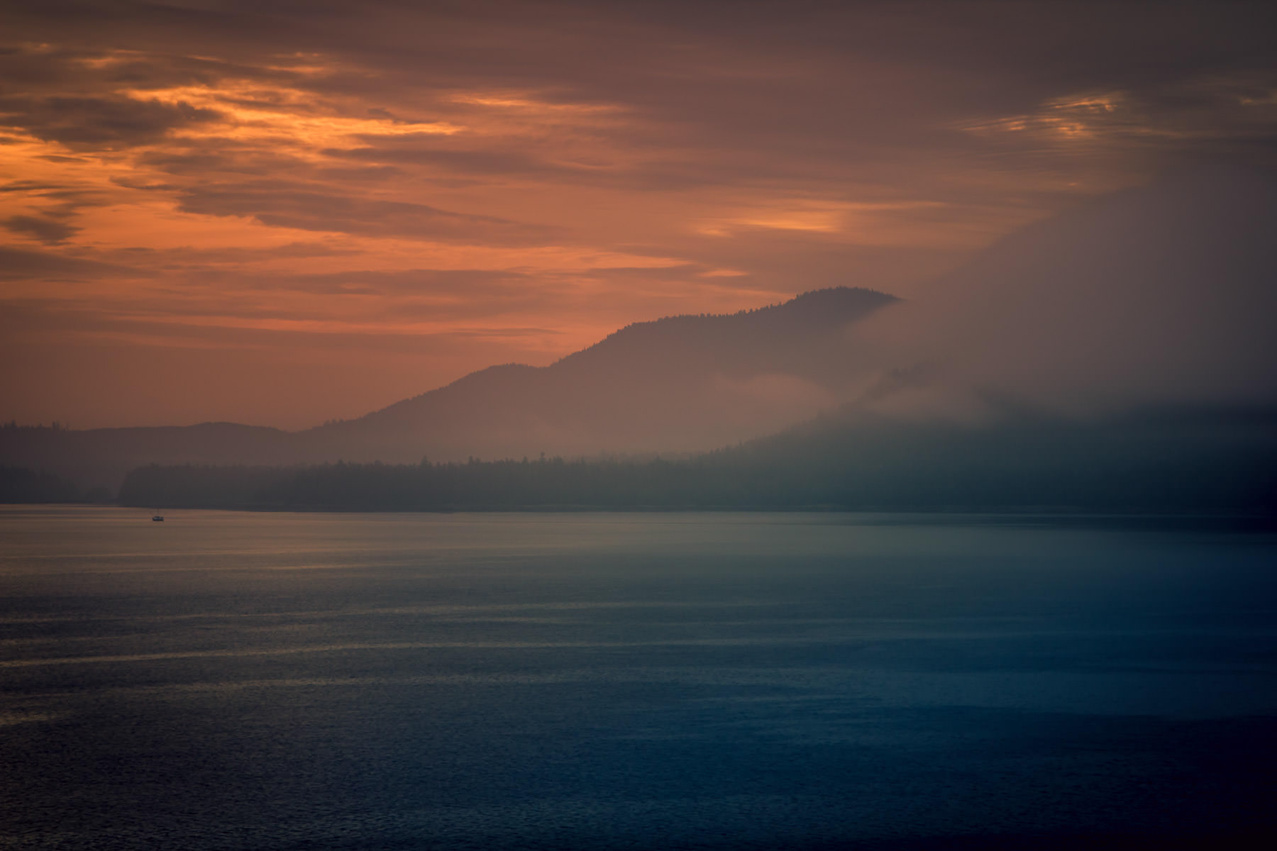 A boat sails Frederick Sound, Alaska, as the sun rises over the surrounding mountains.