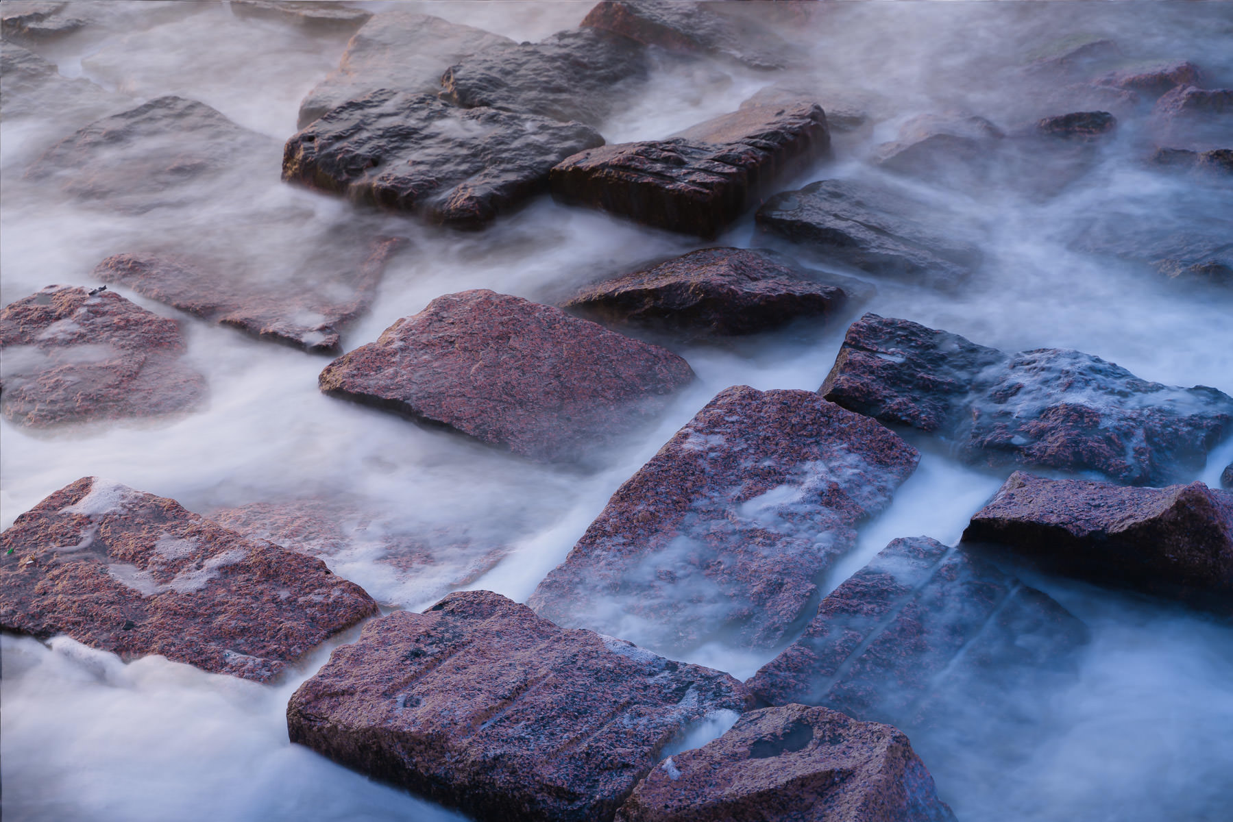 A long exposure renders the surf on these granite blocks soft and fluffy, as spotted along the Galveston, Texas, seawall.