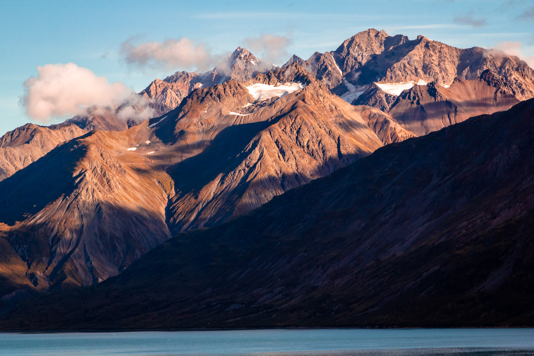 The morning sun illuminates mountains at Alaska's Glacier Bay National Park.