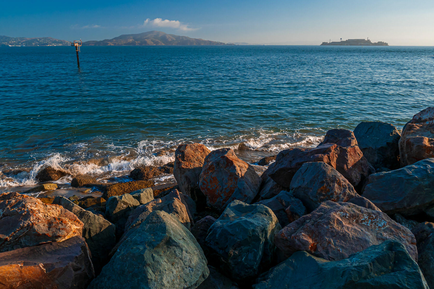 The waters of San Francisco Bay lap at the rocky shore of the Crissy Field beach.