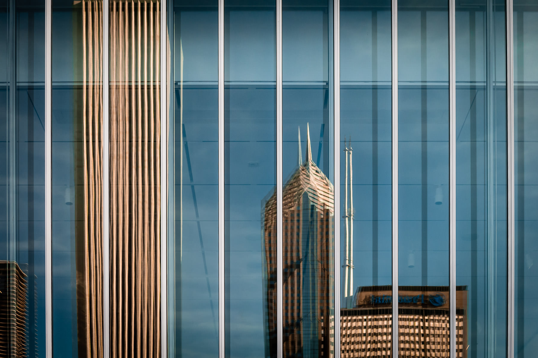 Chicago's Aon Center, Two Prudential Plaza and One Prudential Plaza are reflected in the glass windows of a nearby building.