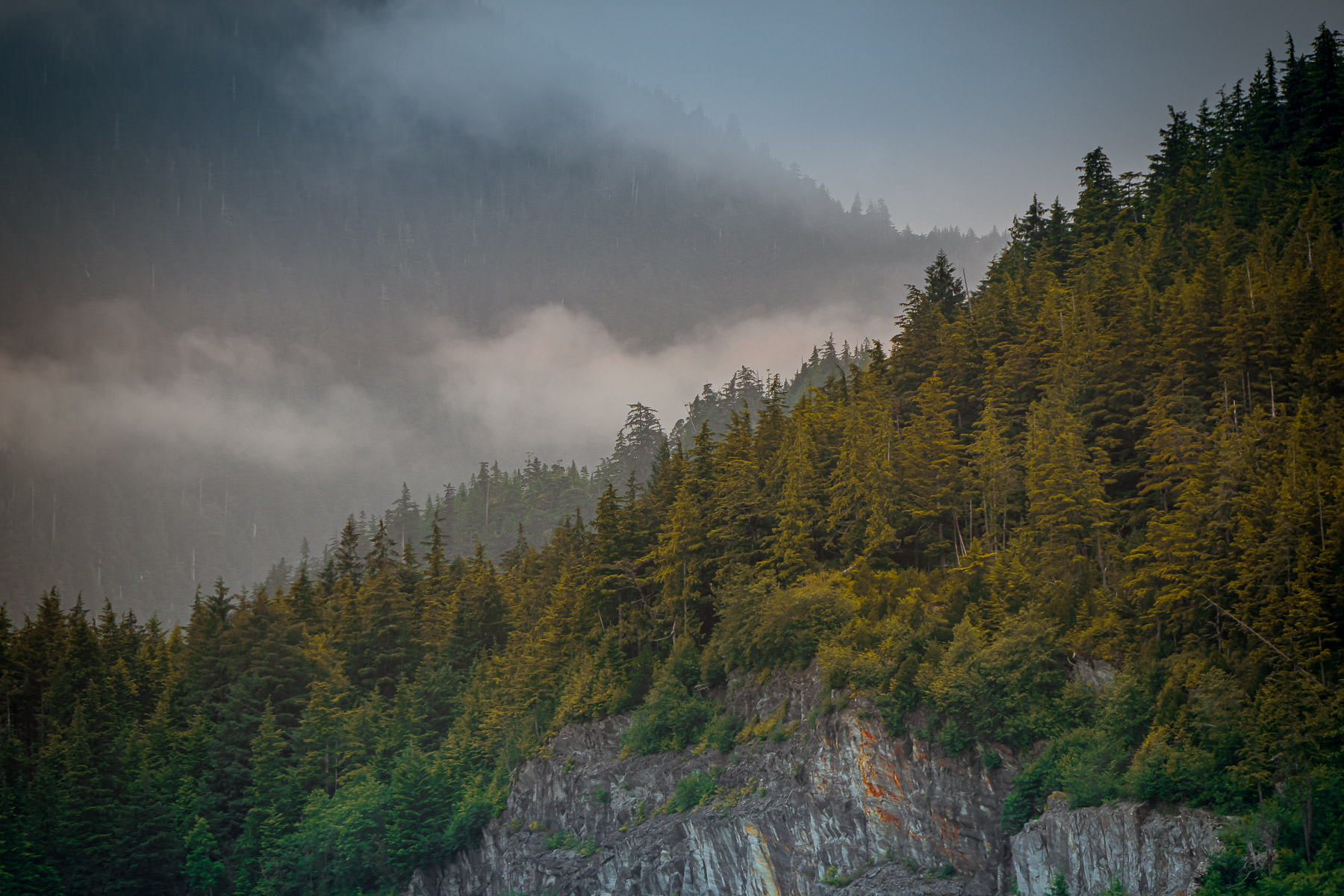 Low-lying clouds begin to dissipate in the mountains above Ketchikan, Alaska