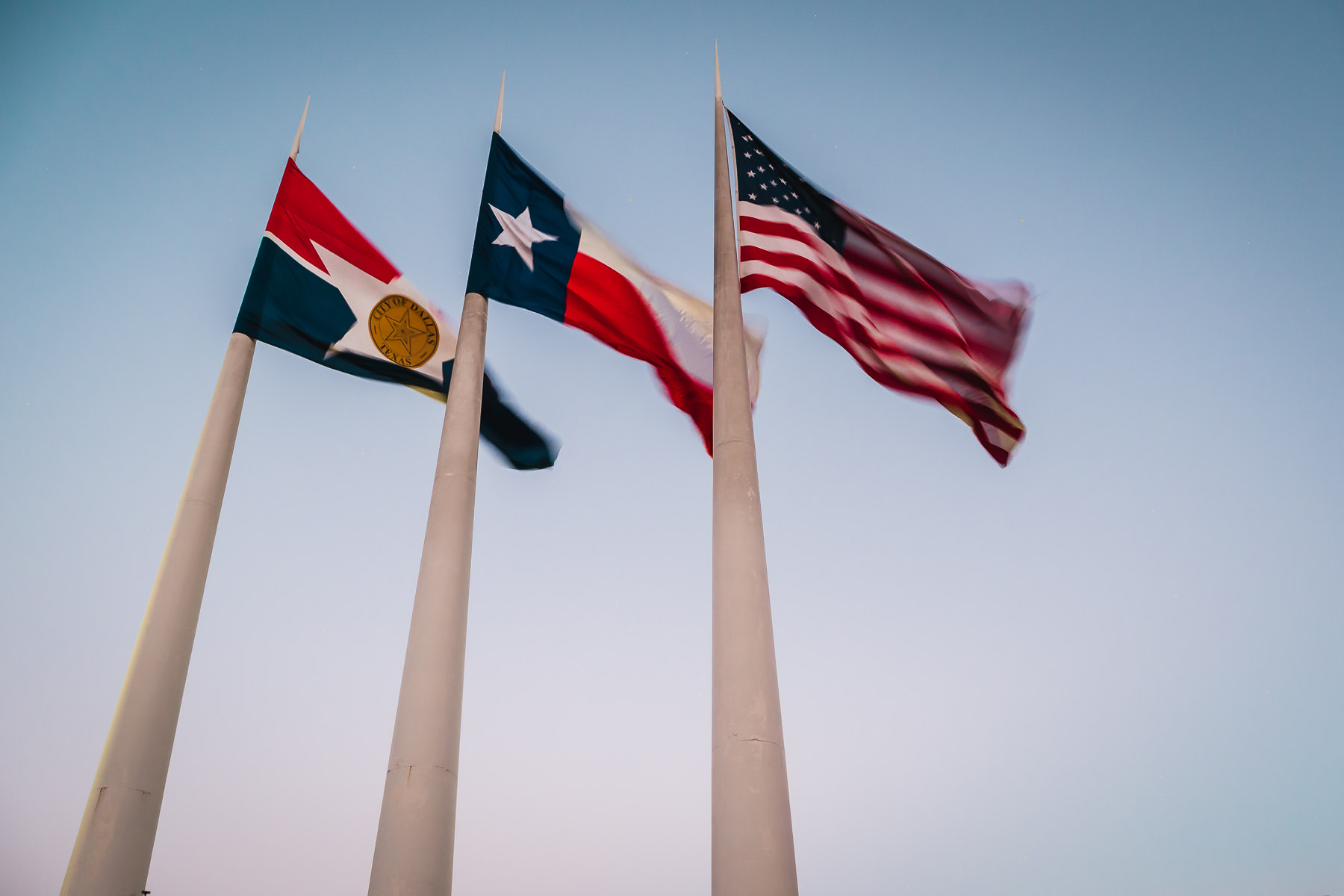 The flags of the City of Dallas, the State of Texas and the United States wave in the evening sky at Dallas City Hall.