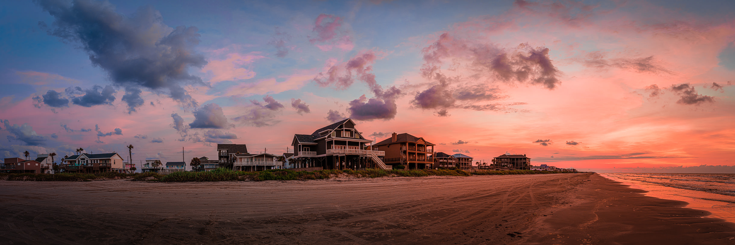 The sun rises on houses along the Galveston, Texas, beach.