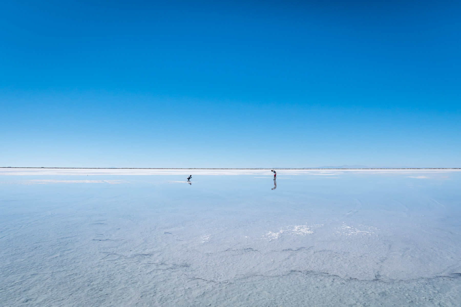 Two visitors to the Bonneville Salt Flats, Utah, stand out among the white expanse.