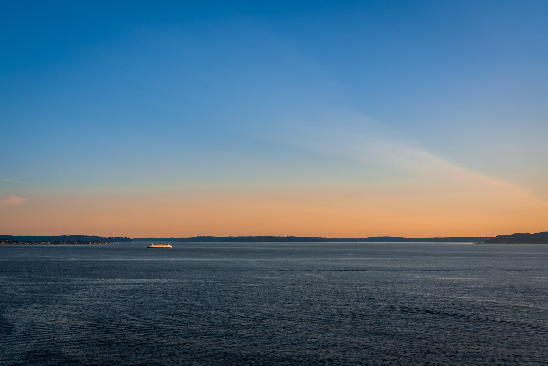 The sun sets on the Seattle-Bainbridge ferry as it crosses Puget Sound.