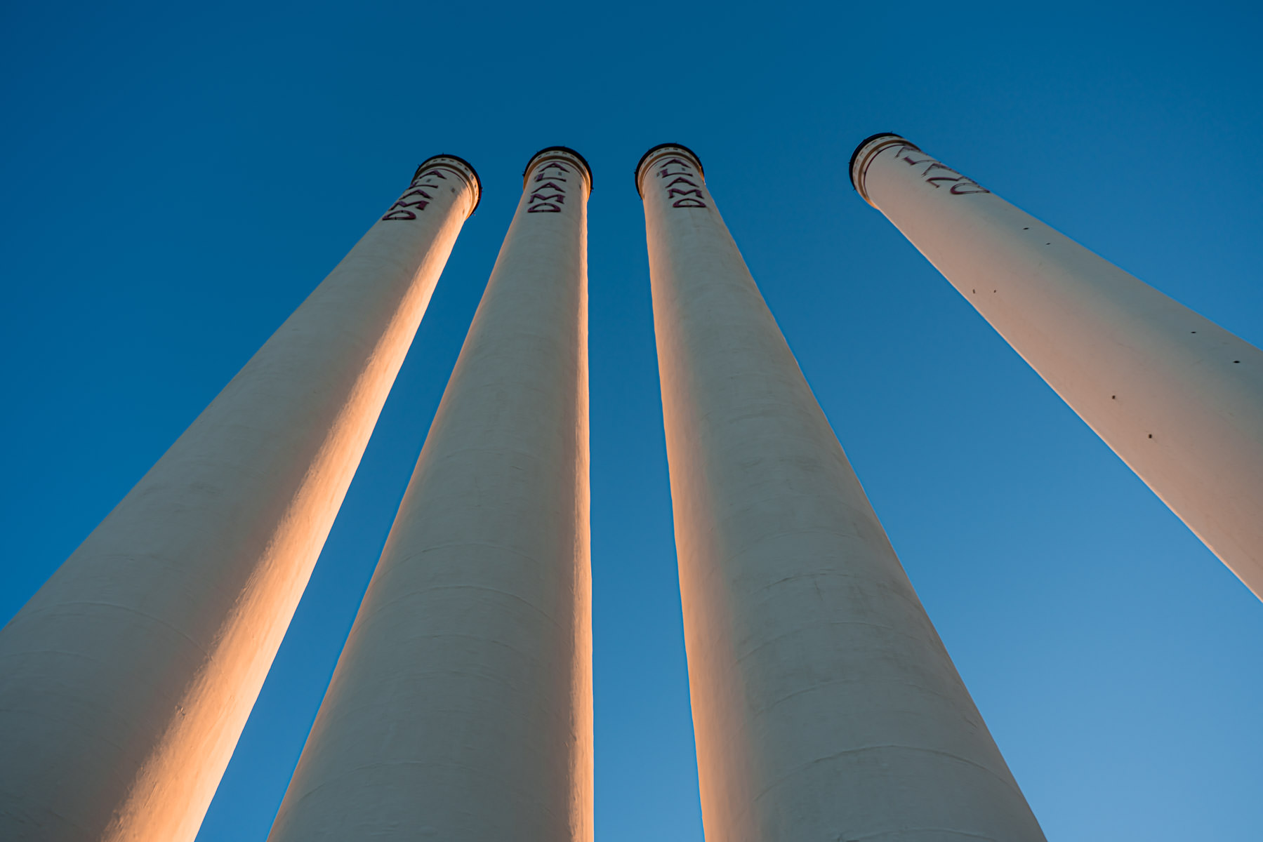 The four 204-foot-tall smokestacks at the Alamo Quarry Market, a former cement factory-turned-shopping center, reach into the clear blue sky over San Antonio, Texas.