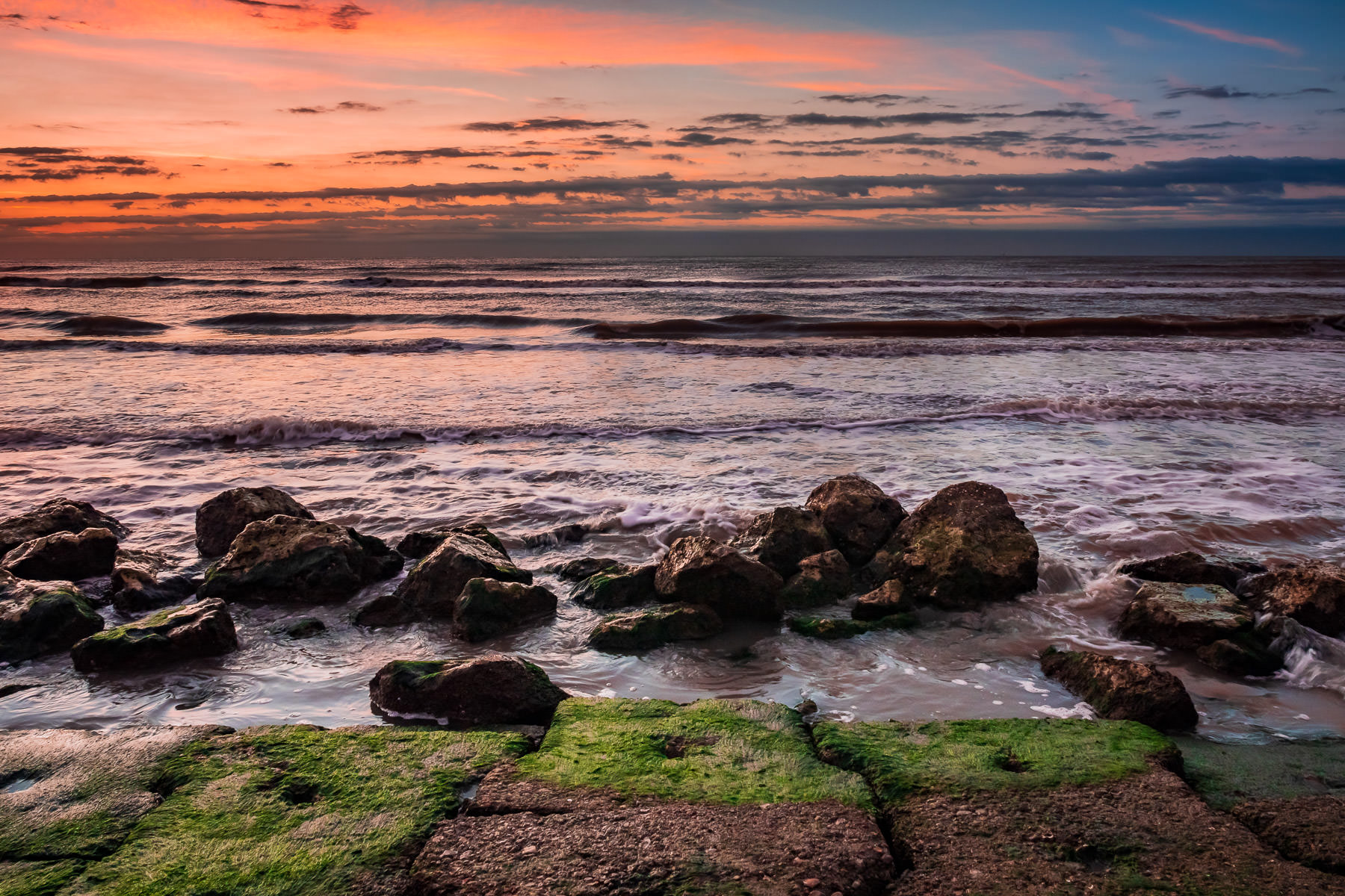 The first light of day hits granite blocks along the beach at the base of the Galveston Seawall, Galveston, Texas.