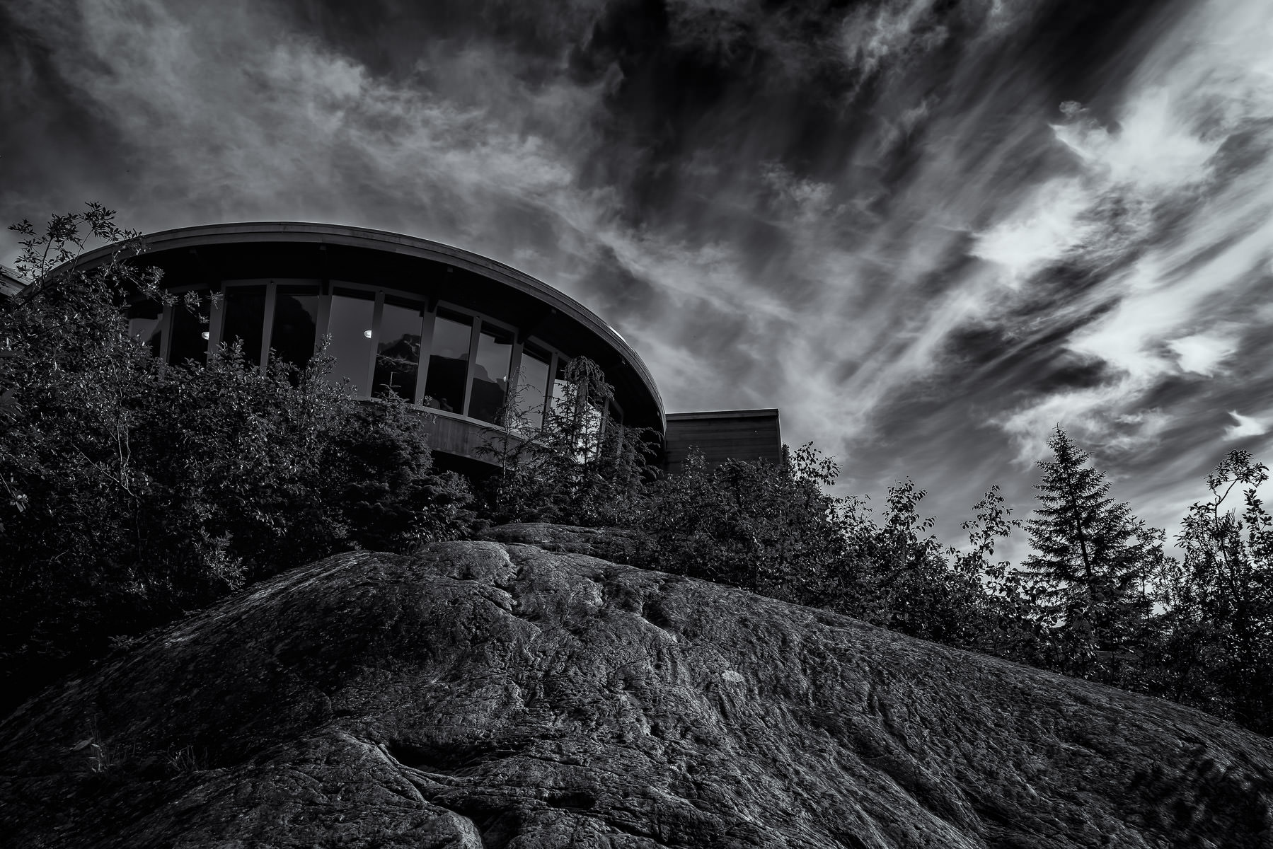The visitors' center at Mendenhall Glacier in Juneau, Alaska, resembles a UFO that has landed atop a rocky outcropping.