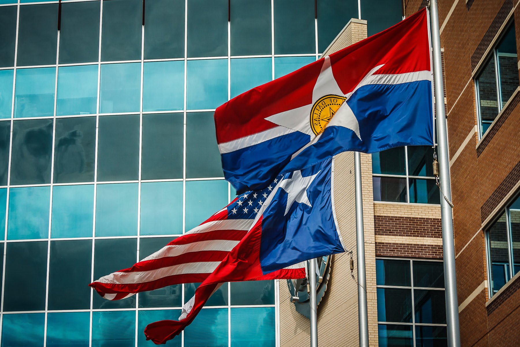 The flags of the City of Dallas, Texas and the United States wave in the wind outside of the Dallas Police Department Headquarters in The Cedars.