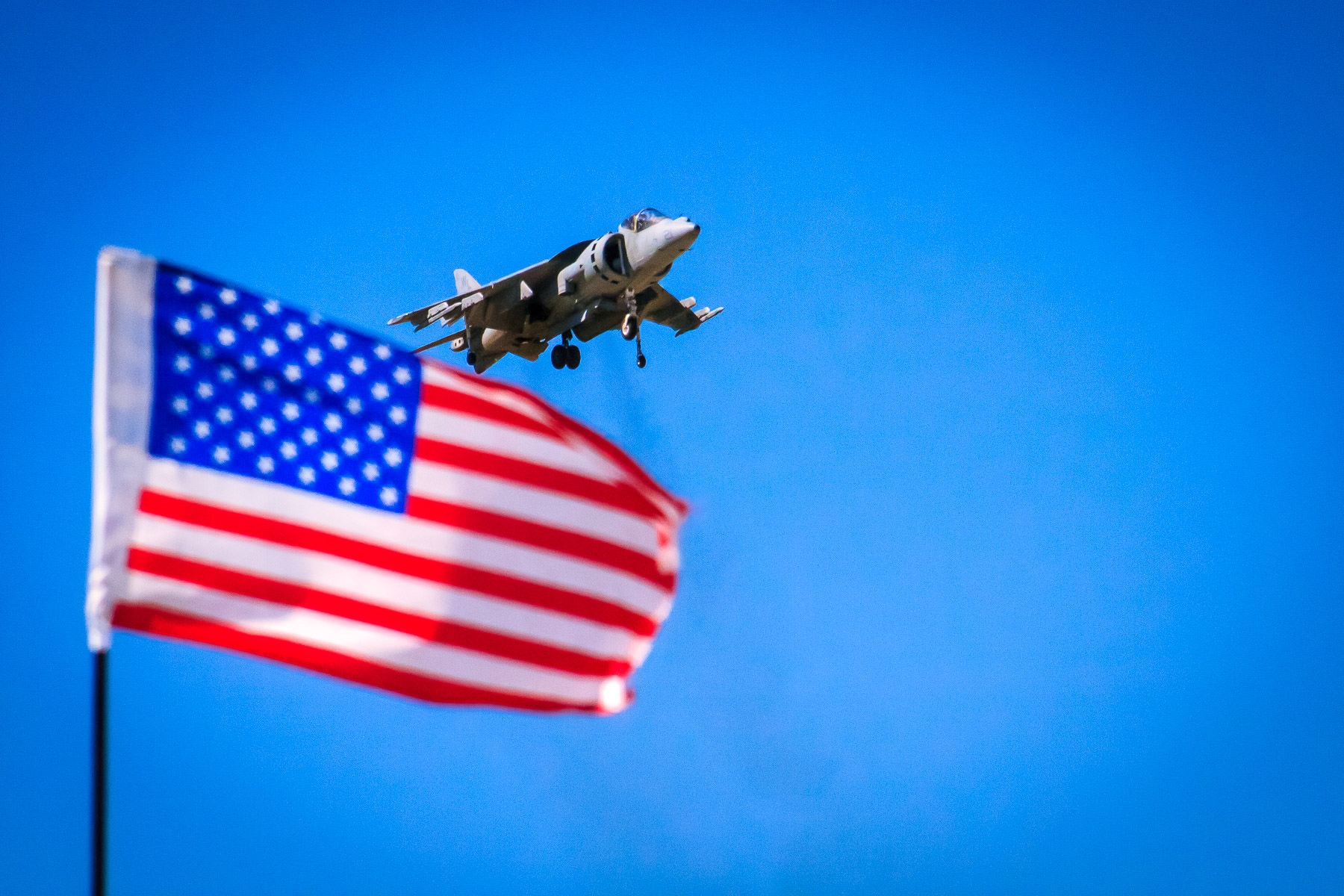 A US Marine Corps AV-8B Harrier II takes off at the Fort Worth-Alliance Air Show while an American Flag waves in the foreground.