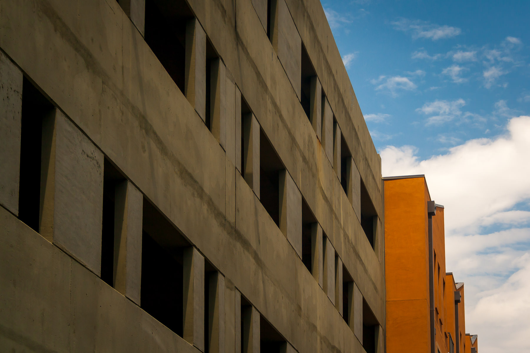 One of the parking garages at Eastside Village in downtown Plano, Texas, next to a bright orange residential building.