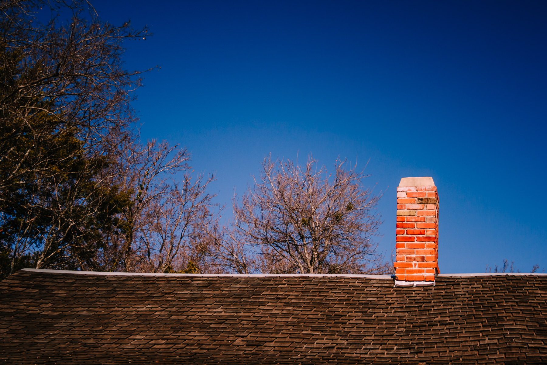 The roofline and chimney of a decaying farmhouse at Penn Farm, Cedar Hill State Park, Texas.