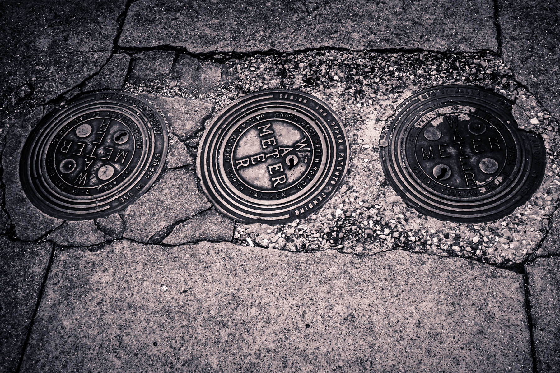 Three water meters embedded in the sidewalk in Downtown Tyler, Texas.