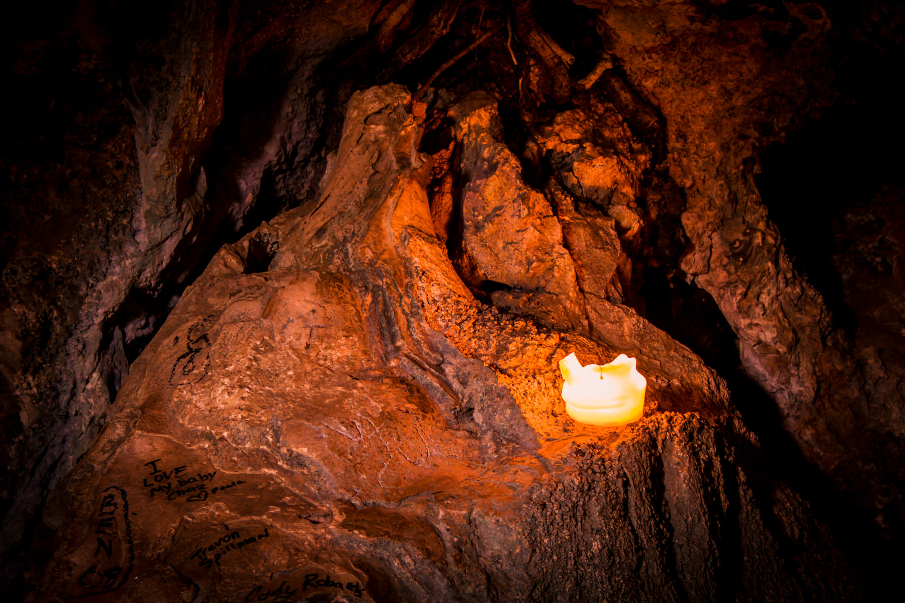 A candle highlights graffiti in a small cave at Turner Falls Park, Oklahoma.