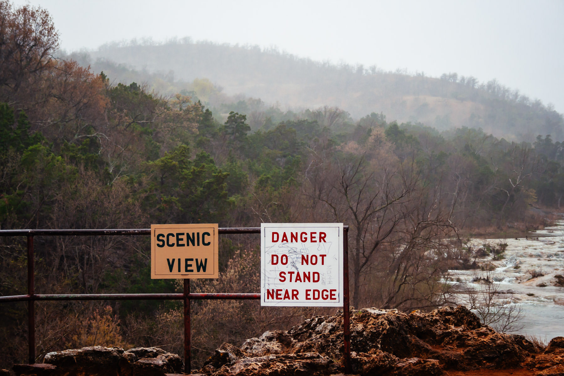 A warning sign at Turner Falls in Oklahoma on an overcast day.