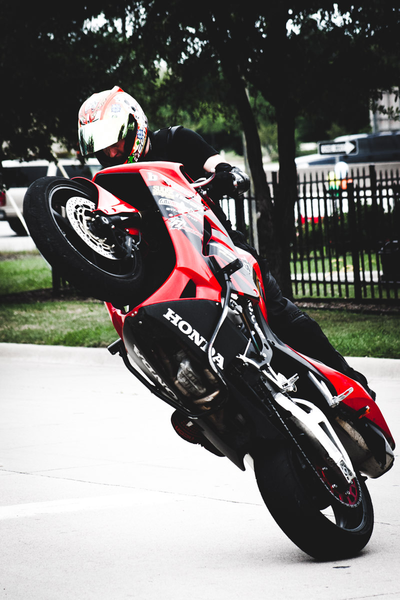 A motorcycle stunt rider shows off at Honda Suzuki North in Dallas.
