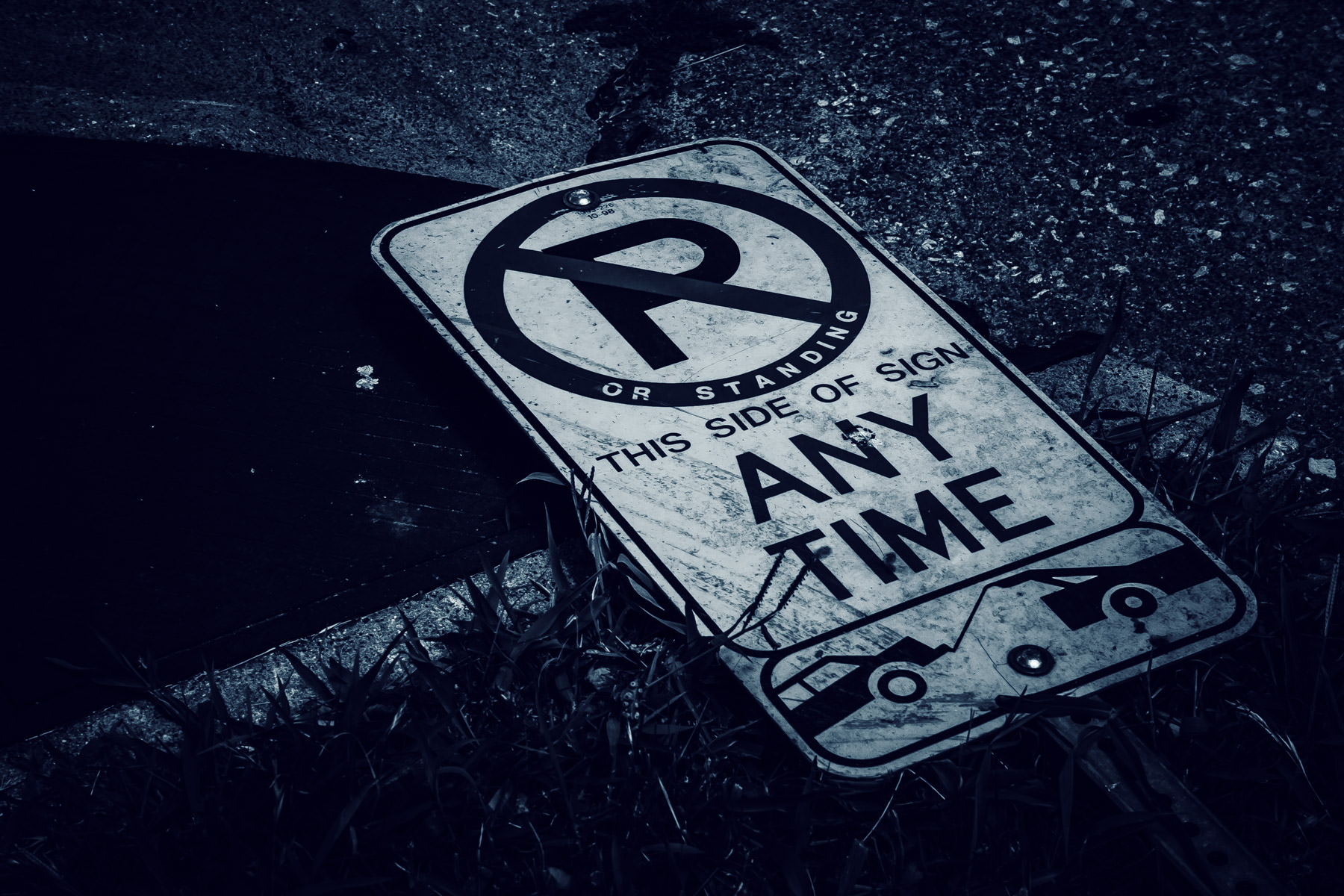 A fallen no parking sign spotted along a road in Uptown Dallas, Texas.