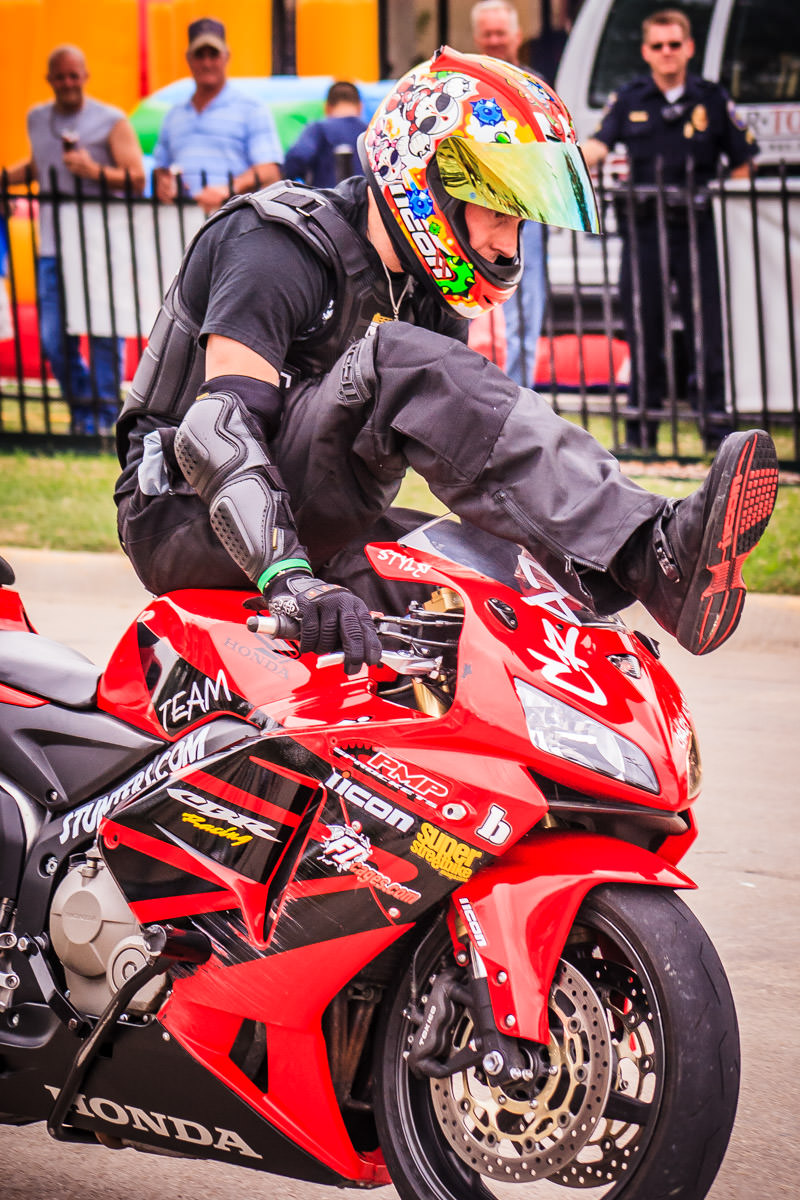 A stunt motorcyclist at Honda-Suzuki North in Dallas.