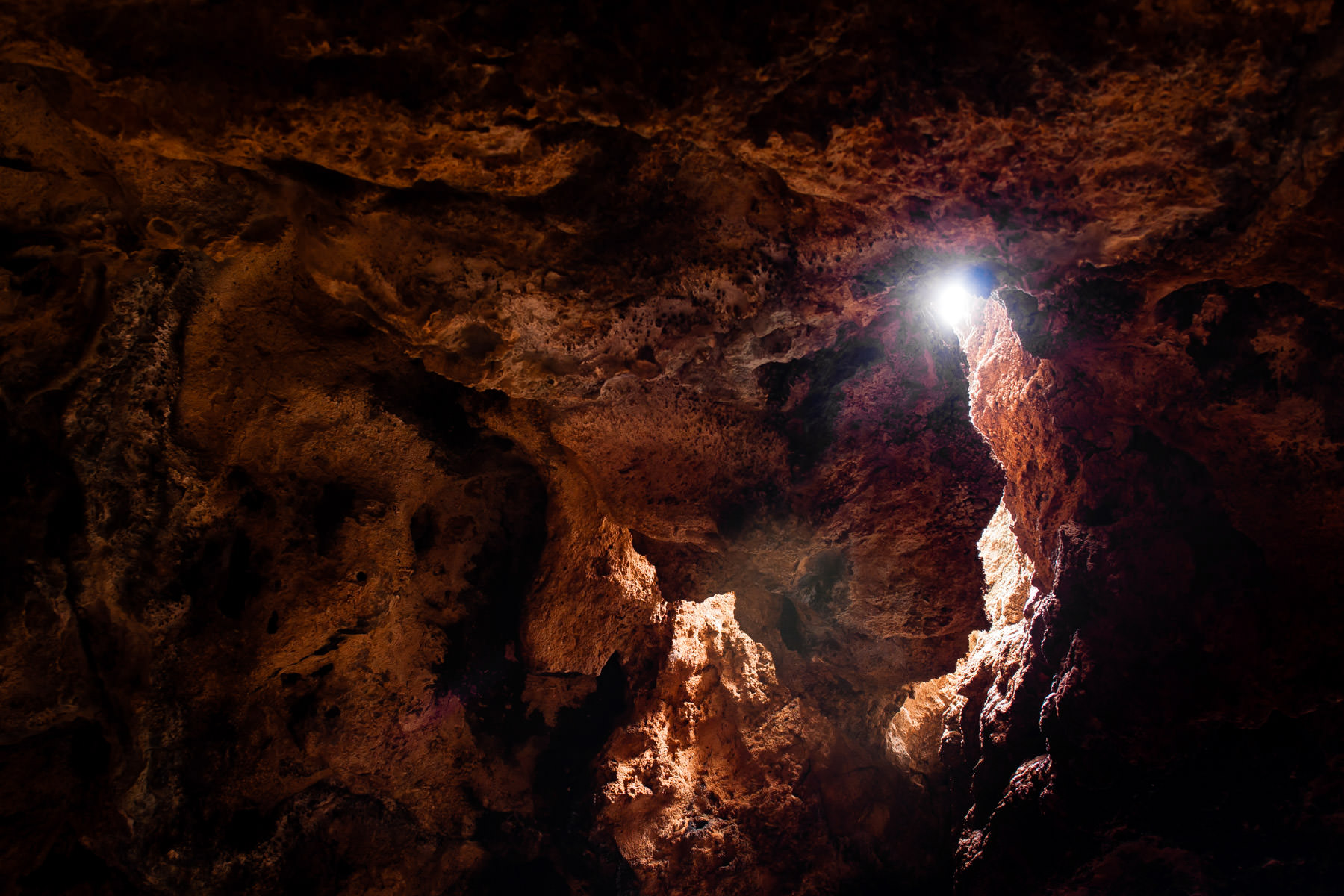 Sunlight streams through a small opening in the roof of a cave at Oklahoma's Turner Falls Park.