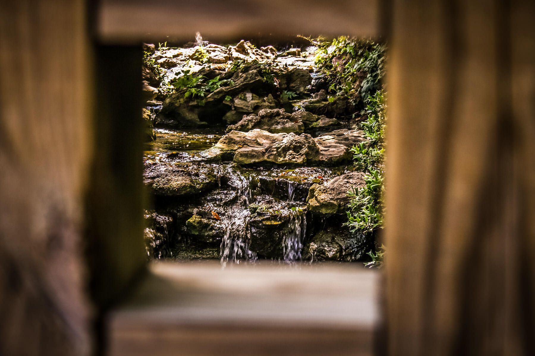 A small waterfall as seen through an opening in a wooden bridge at the Fort Worth Botanical Garden.