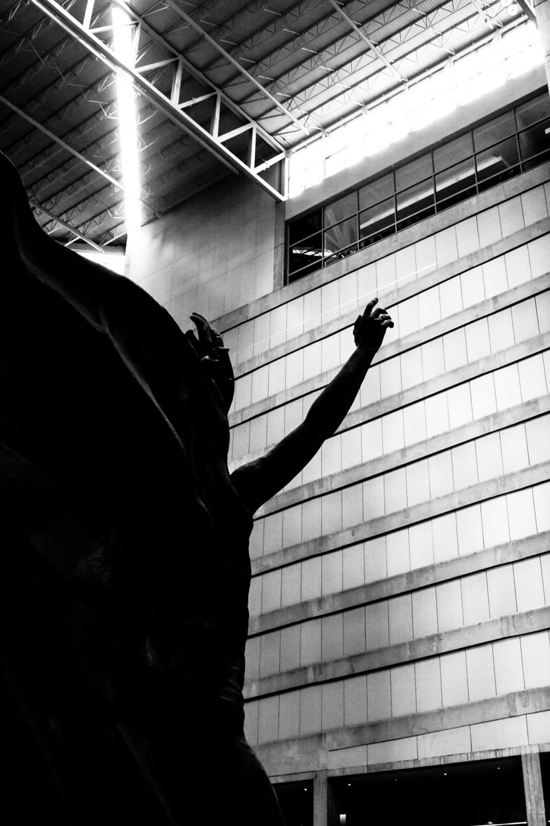 A statue in Dallas' Plaza of the Americas reaches for the atrium's ceiling.