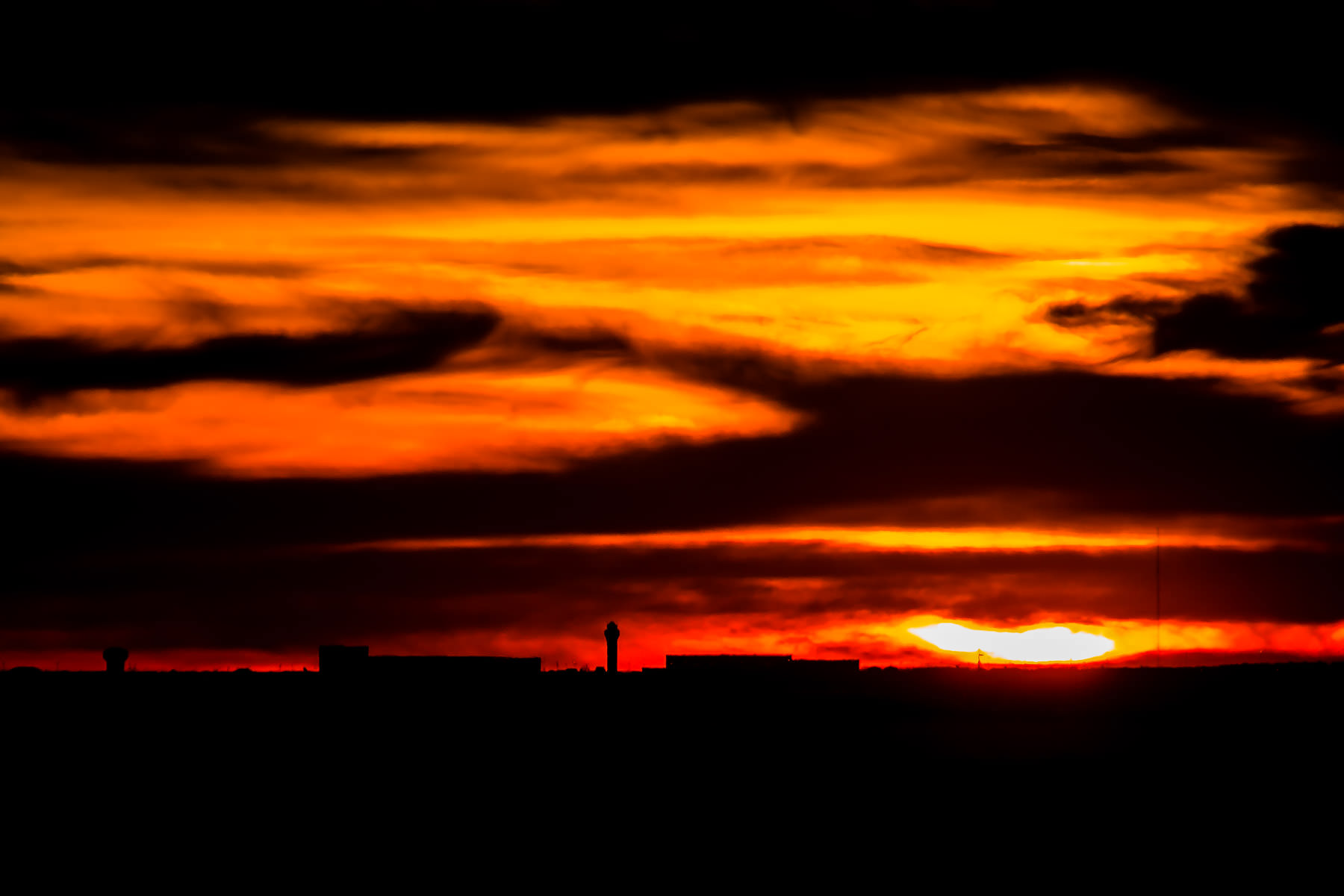 The sun sets behind DFW International Airport as seen from North Dallas.
