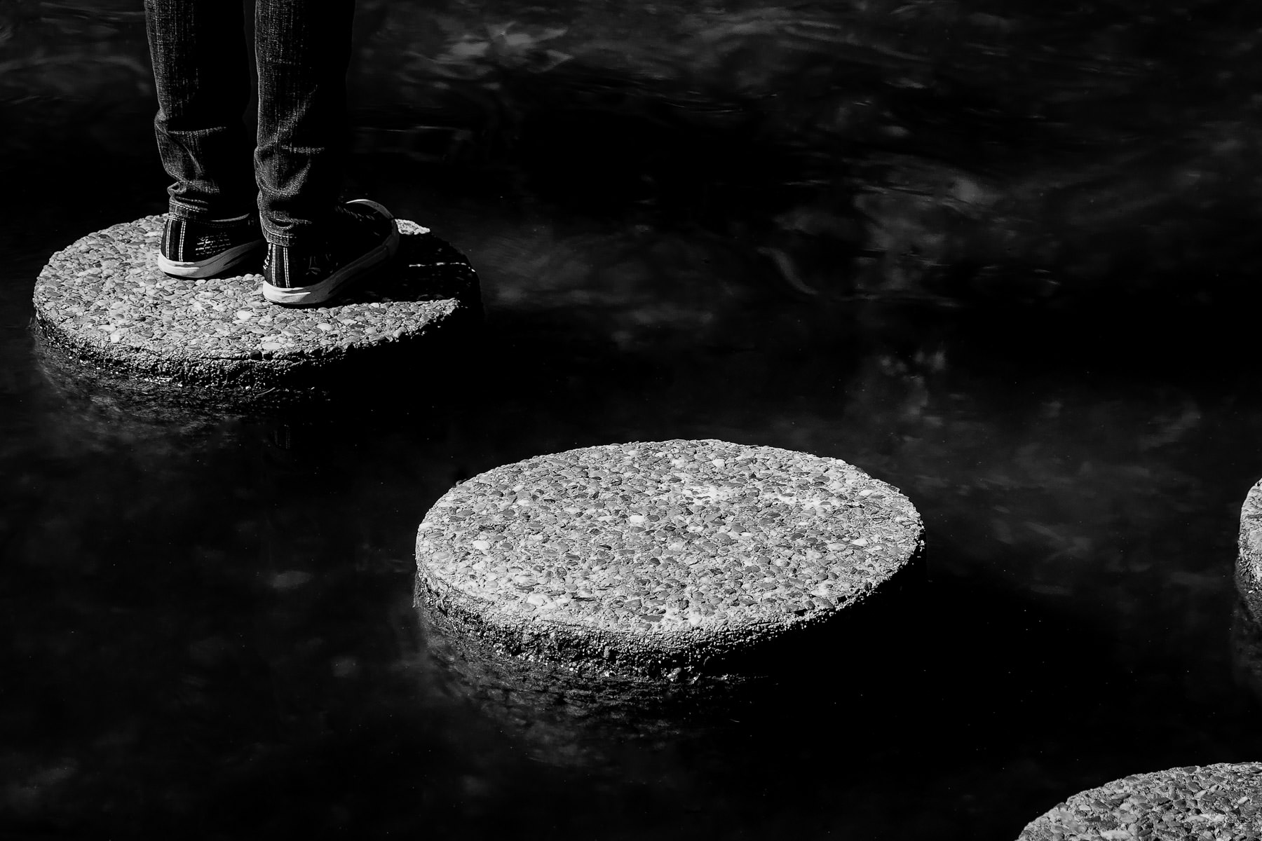 A child stands on stepping stones at the Fort Worth Botanic Gardens.