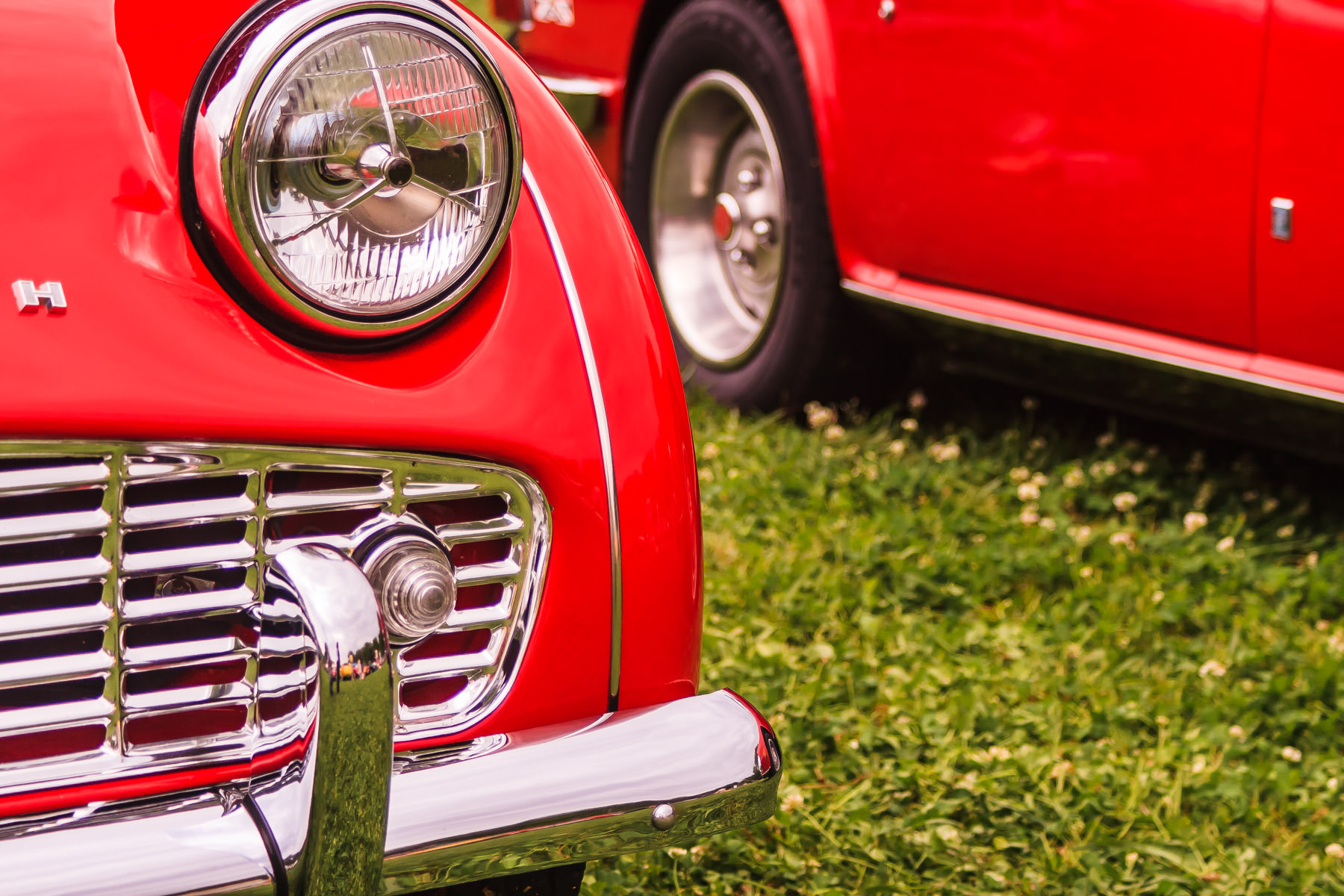 The left headlight of a Triumph TR3A at Dallas' All British and European Car Day.