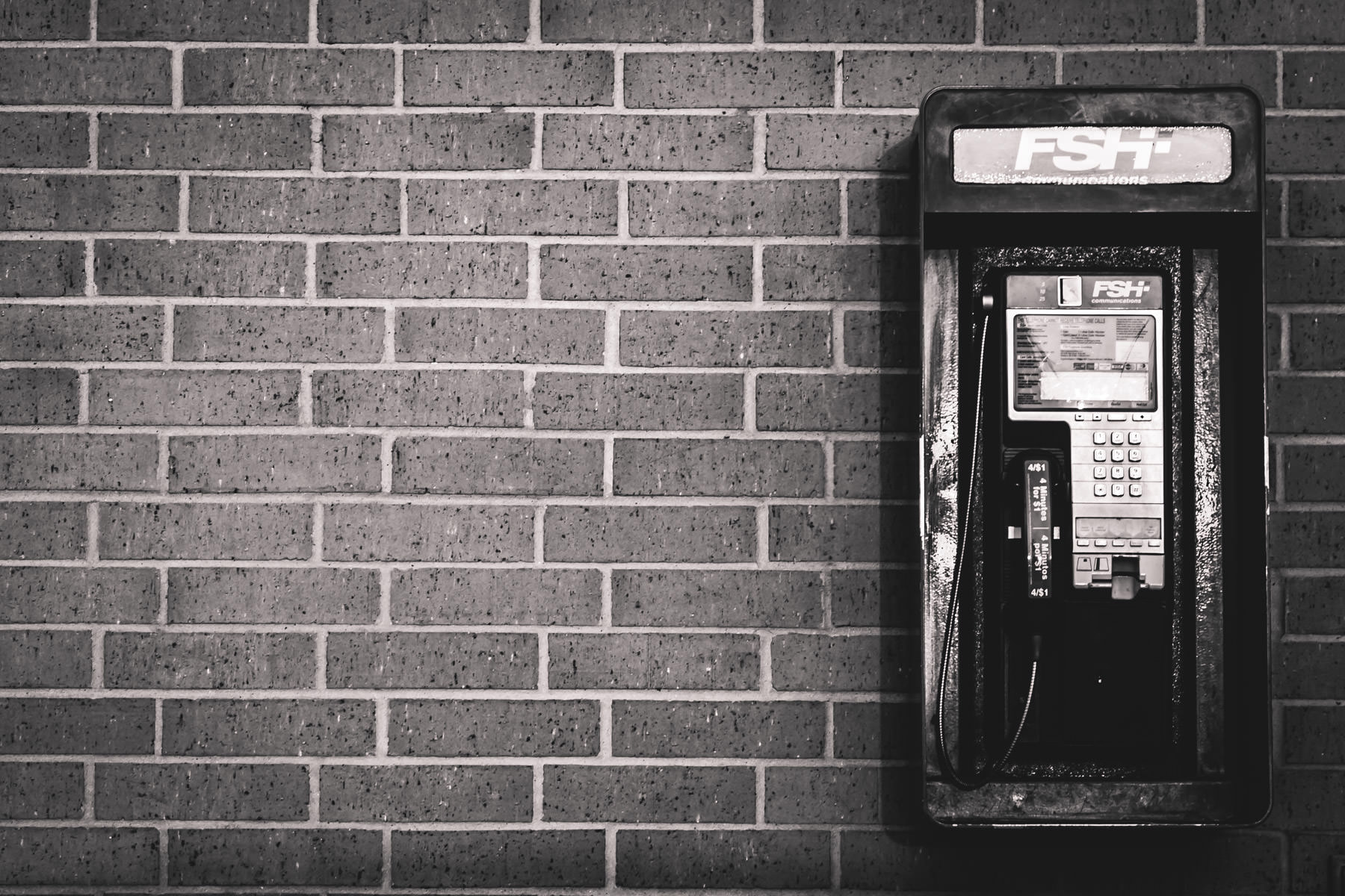 A payphone on the side of a building somewhere in Dallas.