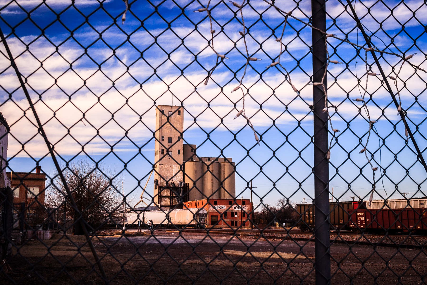 A grain silo seen through a fence on a cold winter day in Wichita Falls, Texas.