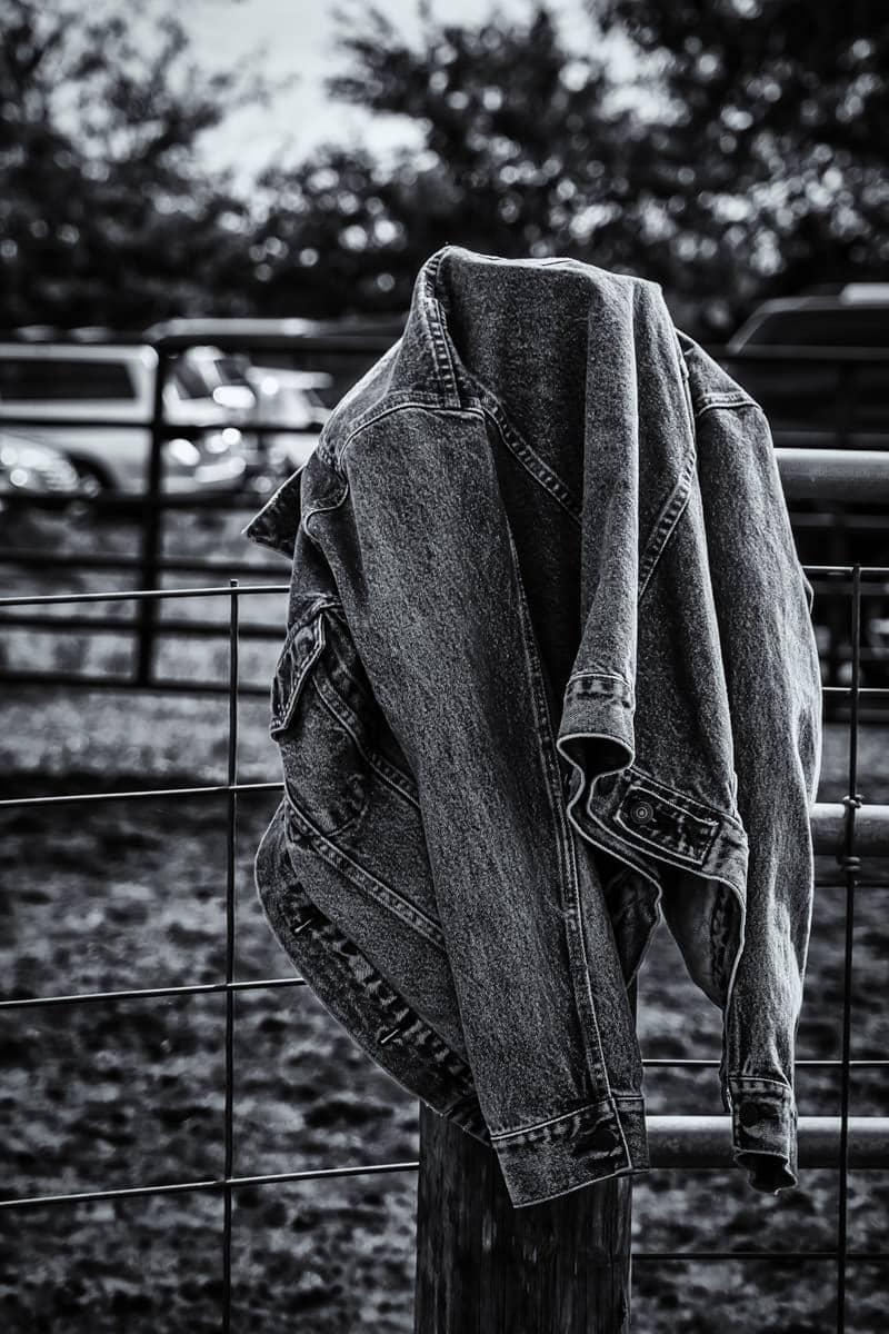 A denim jacket hangs on a fence at Moore Farms in Bullard, Texas.