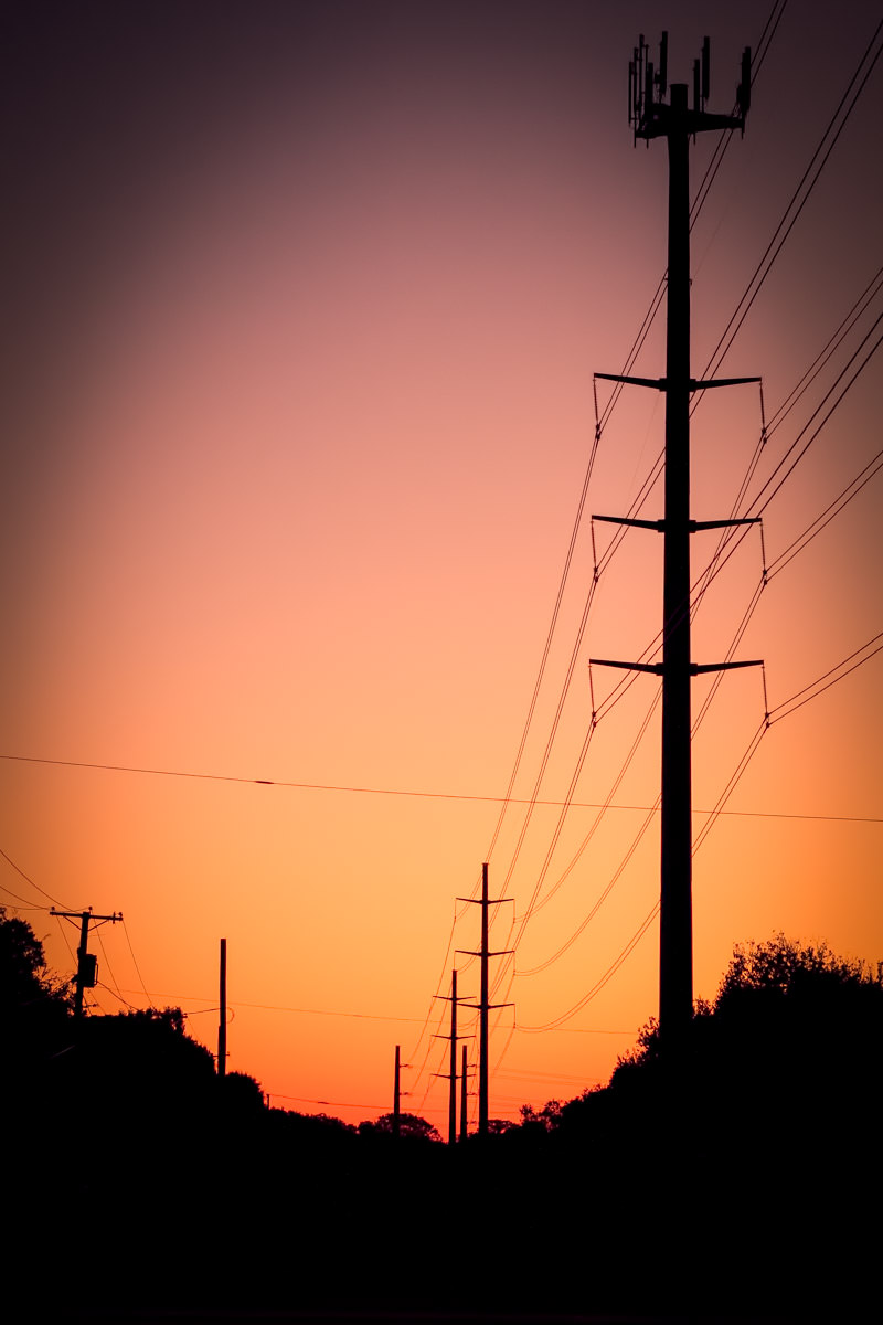 The sun rises behind electric transmission towers and lines in North Dallas.