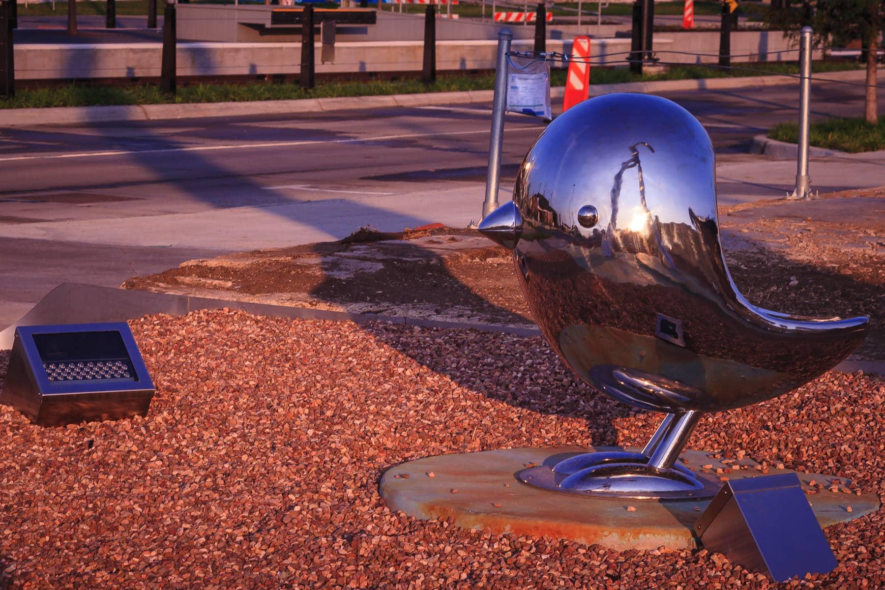 Dallas' Deep Ellum sculpture Traveling Man, is reflected in a companion bird.