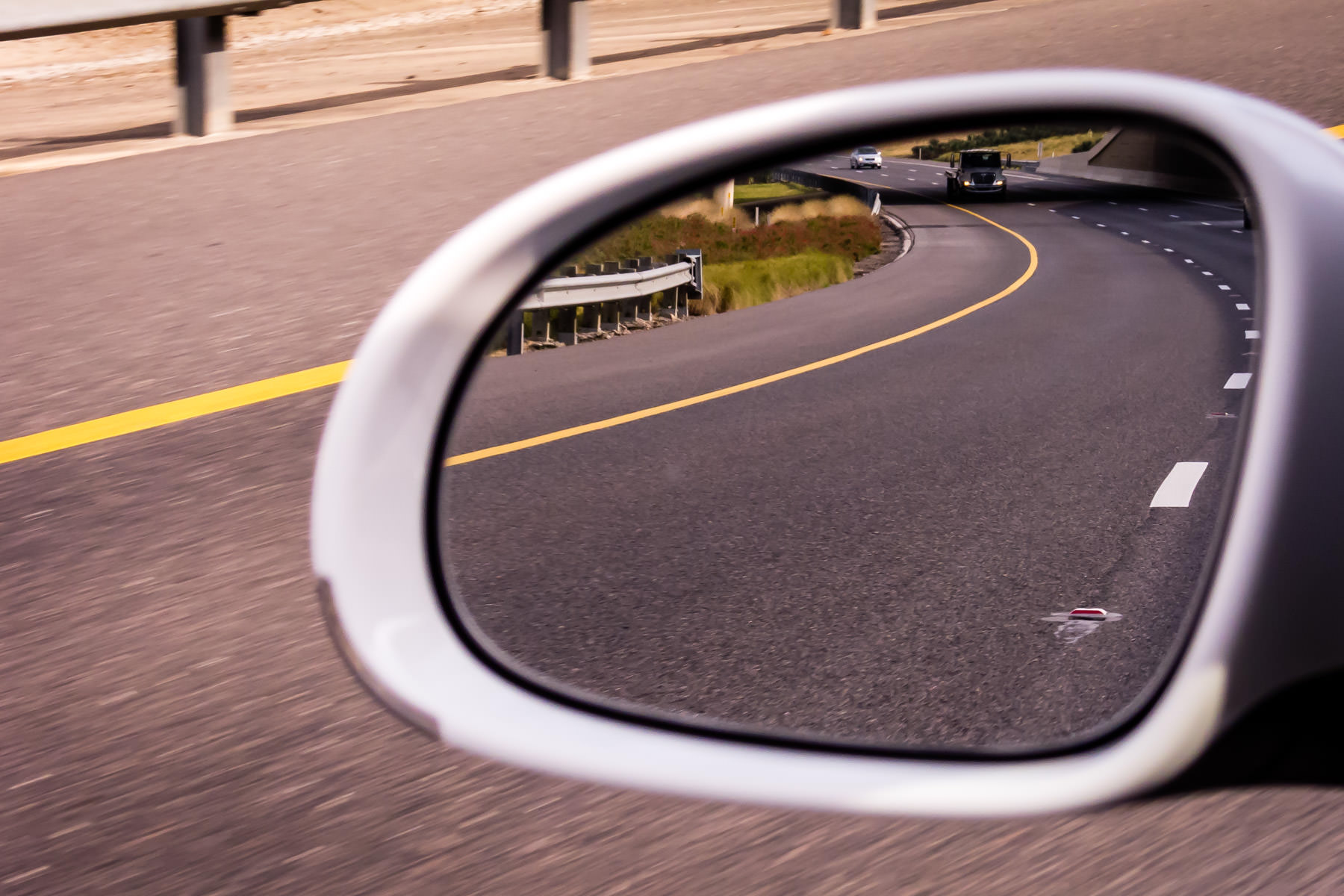 The President George Bush Turnpike in Dallas reflected in the mirror of a Volkswagen GTI.