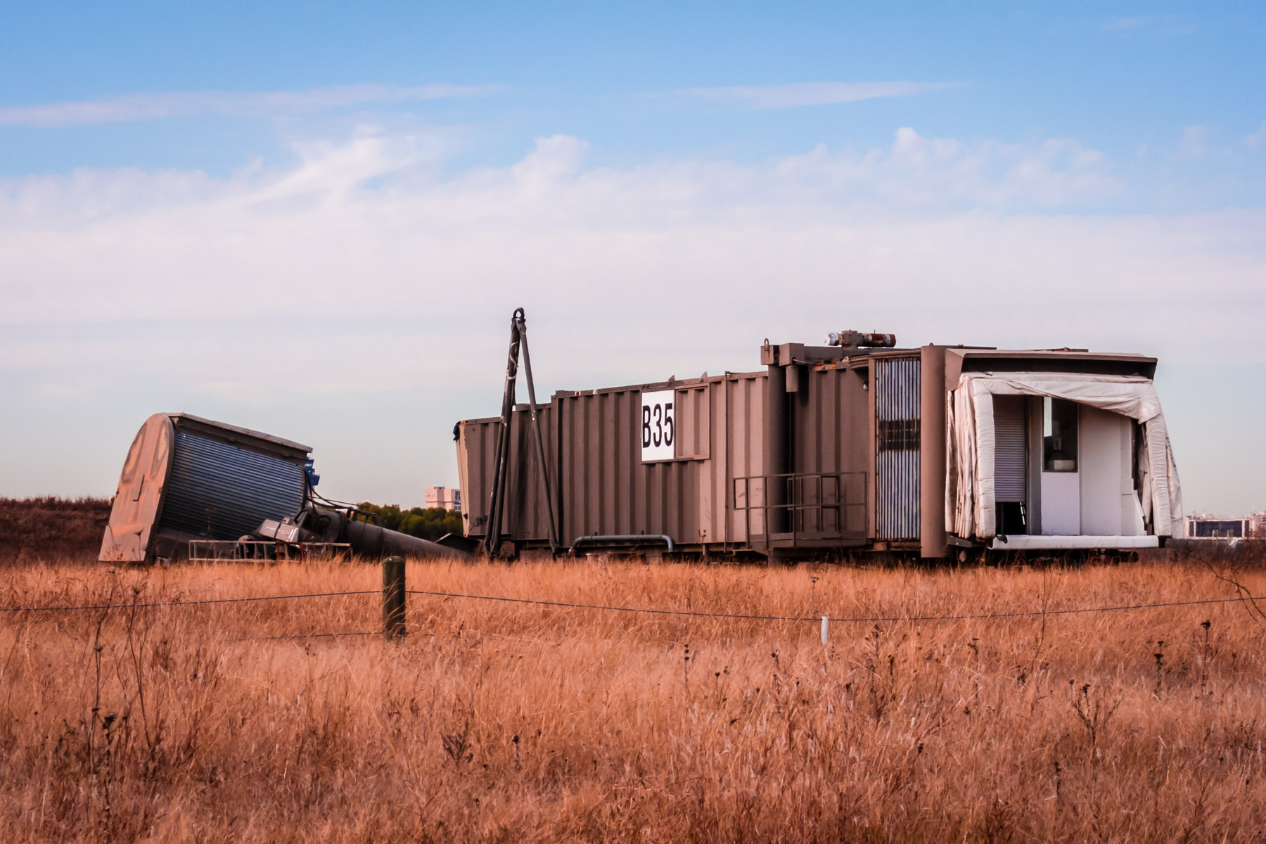 An abandoned jetway lies discarded on the periphery of DFW International Airport.