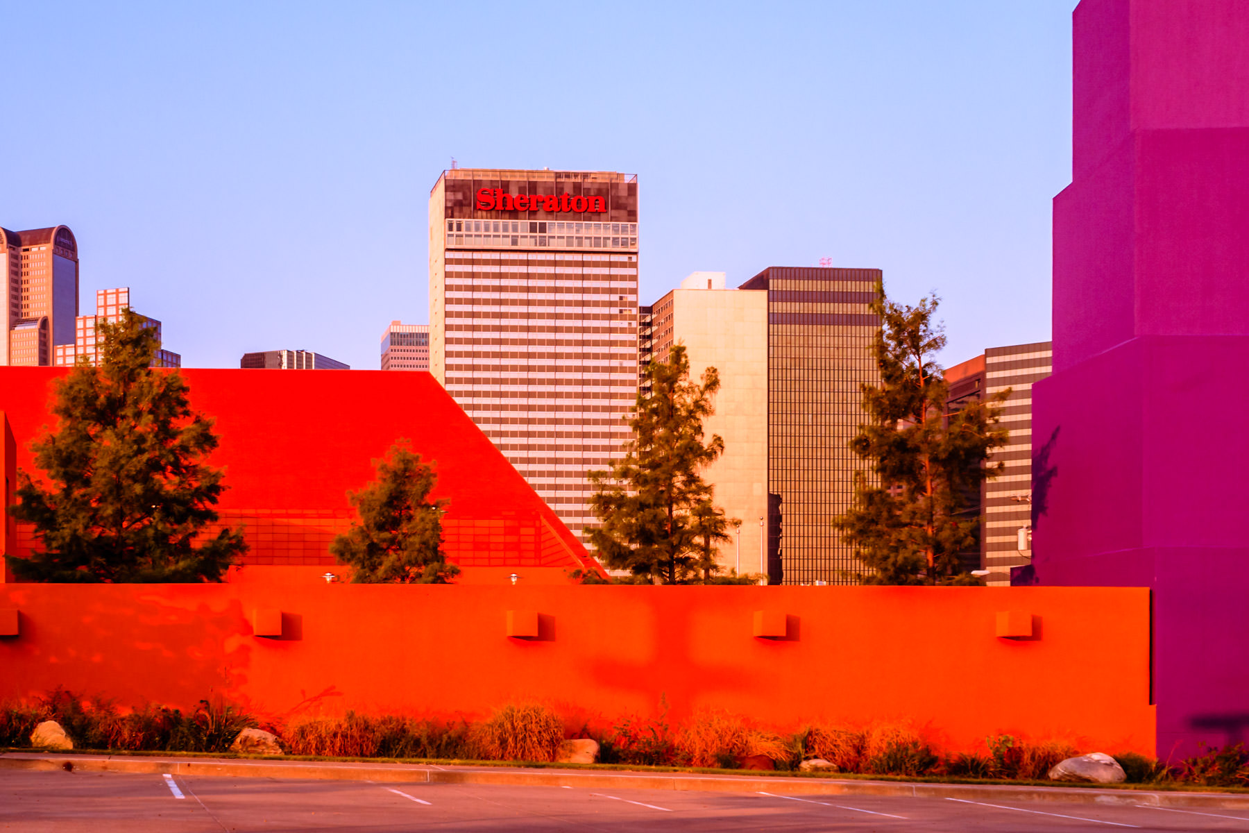 The Downtown Dallas Sheraton Hotel seems to peek over the colorful walls of Deep Ellum's Latino Cultural Center.